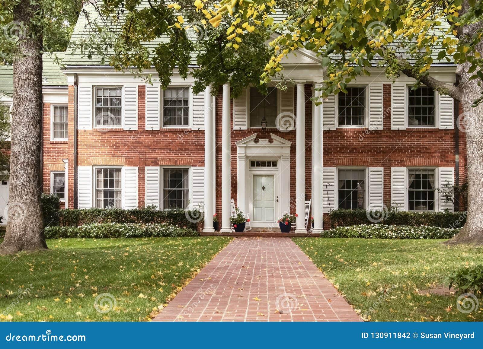 边路导致有白色快门和专栏和摇椅的高级房子在门廊通过高大的树木和绿草sca