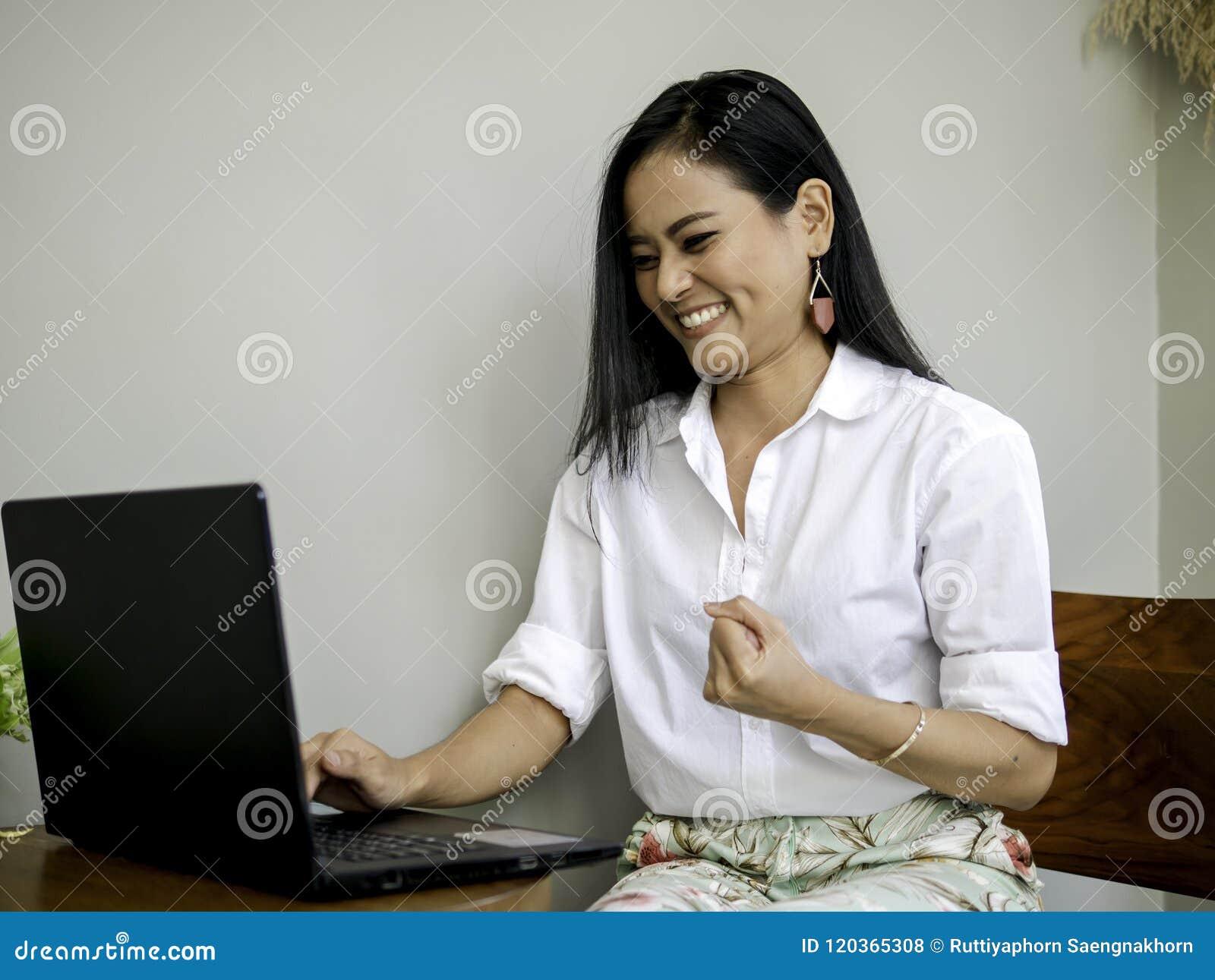 达到目标的成功的美丽的亚裔企业家,举在拳头的手有令人激动的和微笑的面孔的