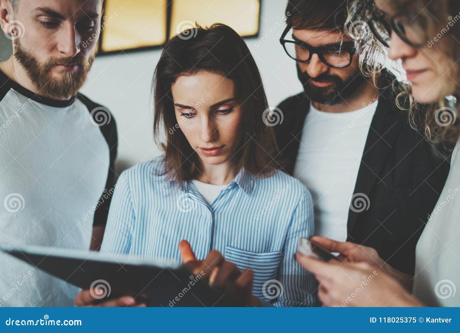 运作的片刻照片 一起使用电子触摸板的小组年轻工友在现代办公室顶楼