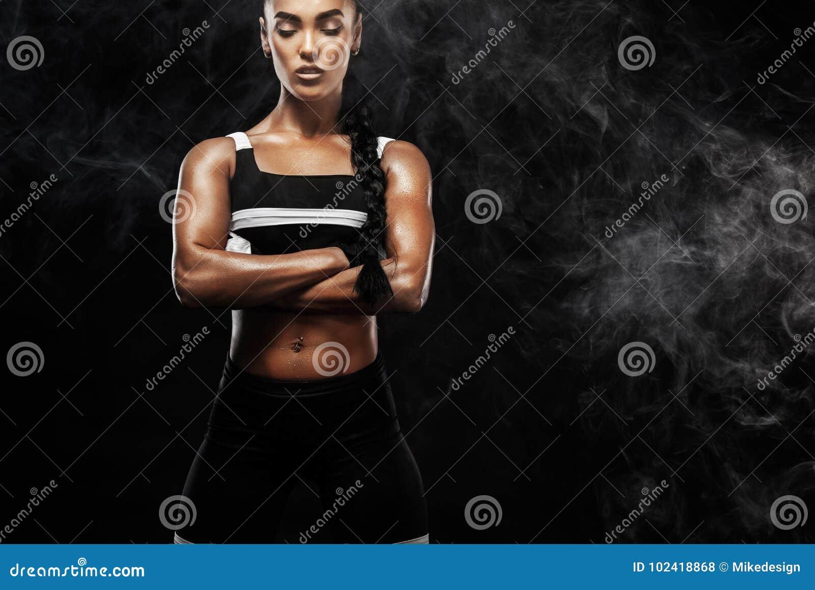 运动的美好的美国黑人的模型, sportwear的妇女做健身行使在黑背景的停留适合