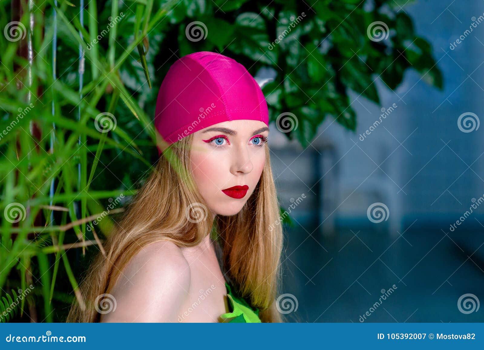 运动美丽的可爱的白肤金发的妇女画象与在游泳盖帽和衣服组成在游泳池