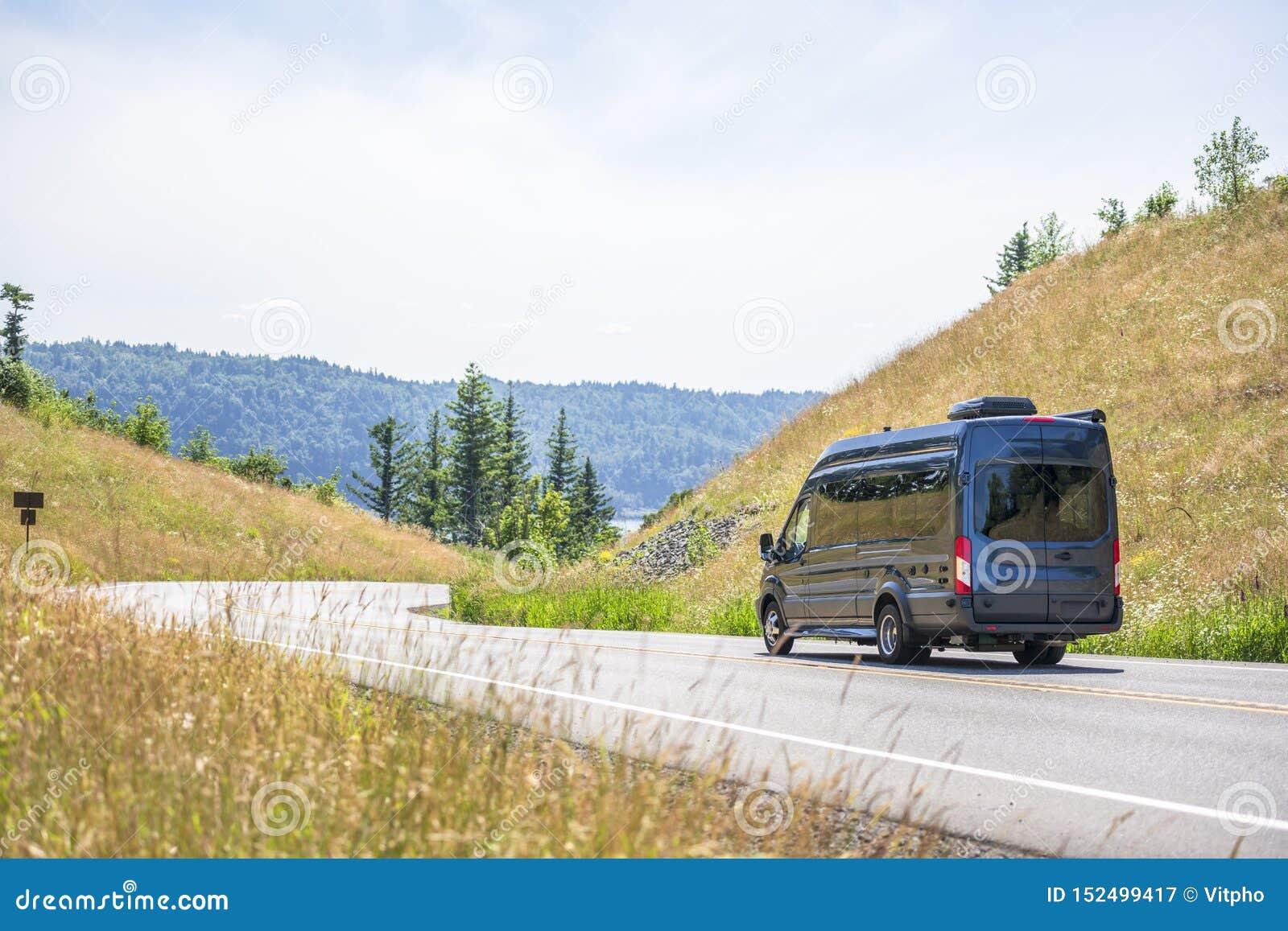 运行在弯曲道路的深灰紧凑商业微型搬运车在小山之间