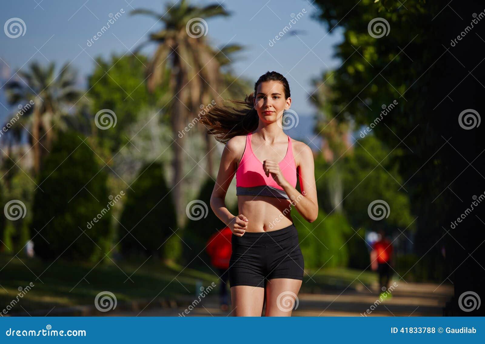 运行在美好的棕榈背景的公园的明亮的运动服的可爱的少妇