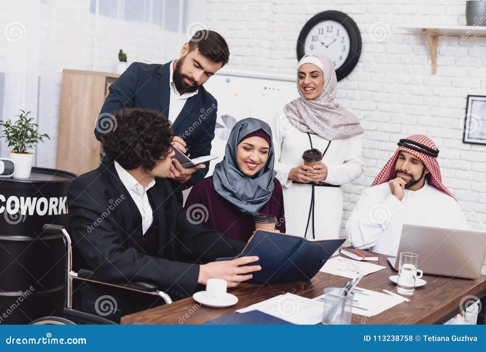 运转在办公室的轮椅的残疾阿拉伯人 人与工友分享笔记