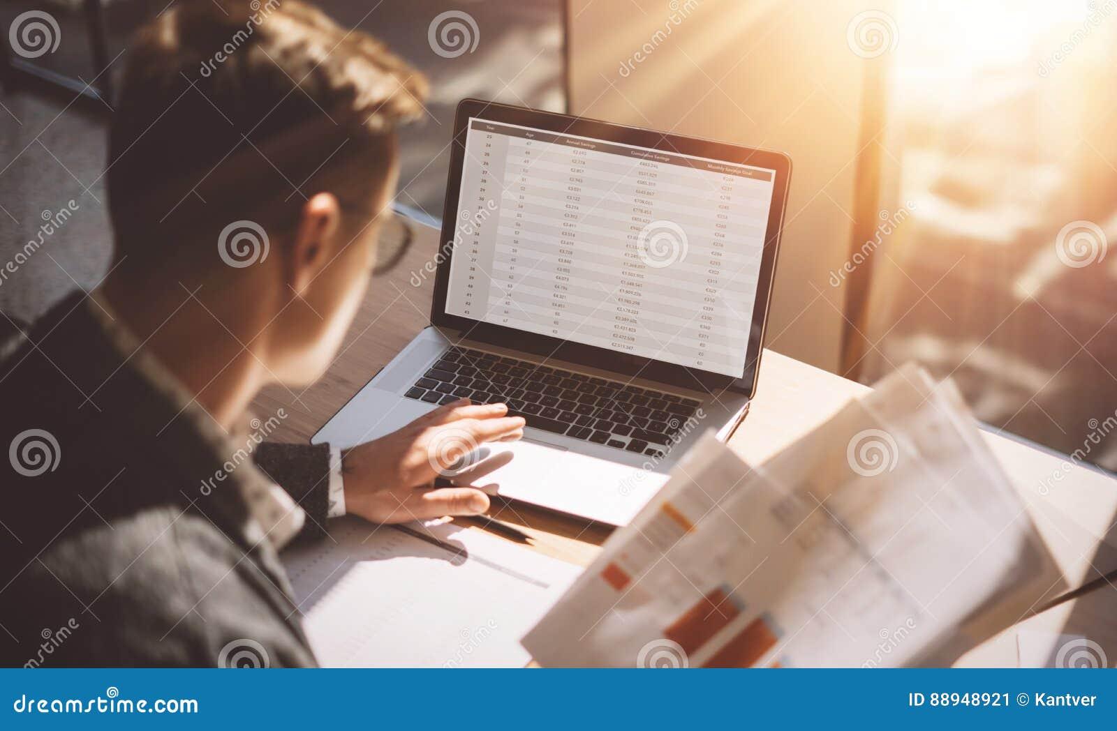 运转在膝上型计算机的晴朗的办公室的镜片的年轻银行业务财务分析家,当坐在木桌上时 商人