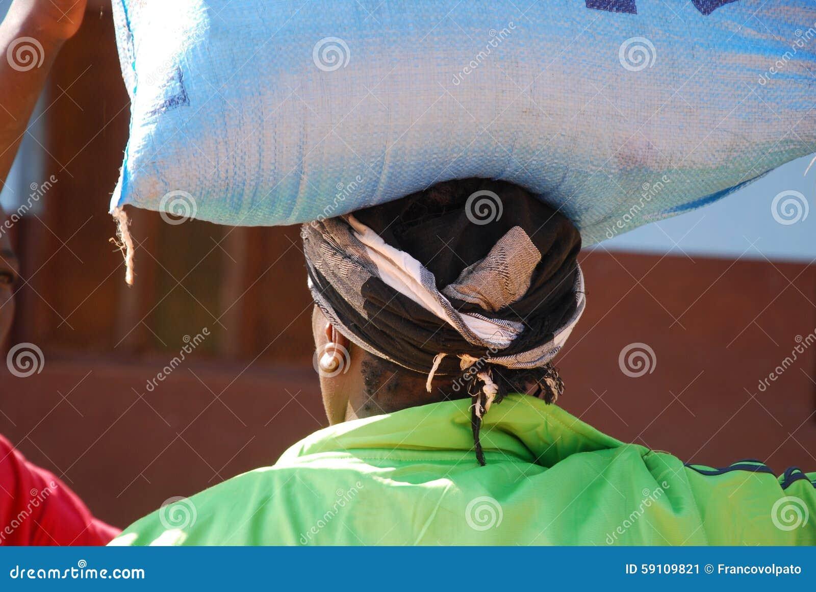 运载一个大袋在头的糖的非洲妇女