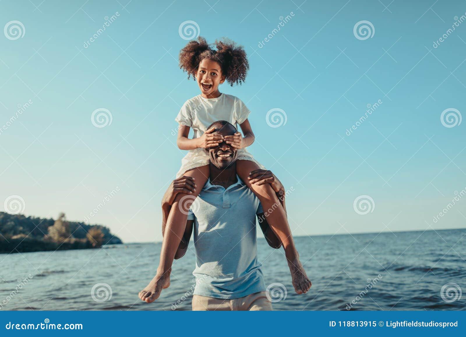 运载可爱的矮小的女儿的微笑的非裔美国人的父亲