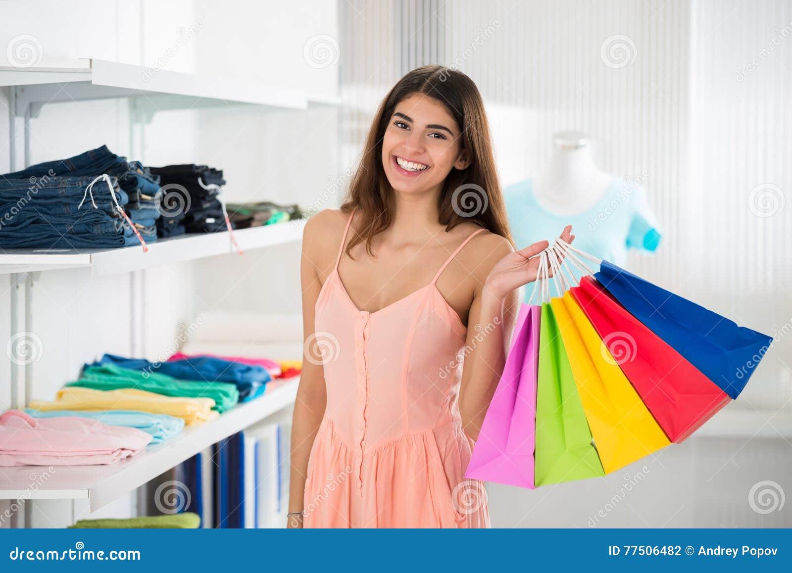 运载在服装店的微笑的妇女五颜六色的购物袋