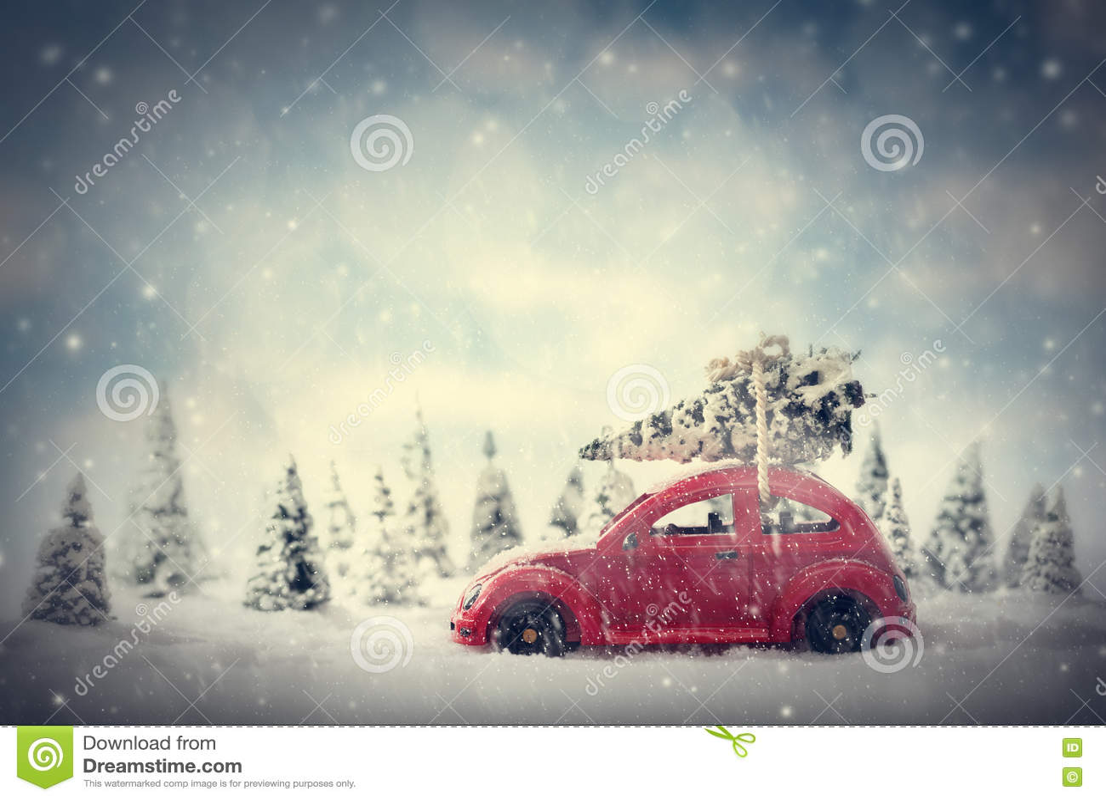 运载微小的圣诞树的减速火箭的玩具汽车 与雪和森林的童话风景