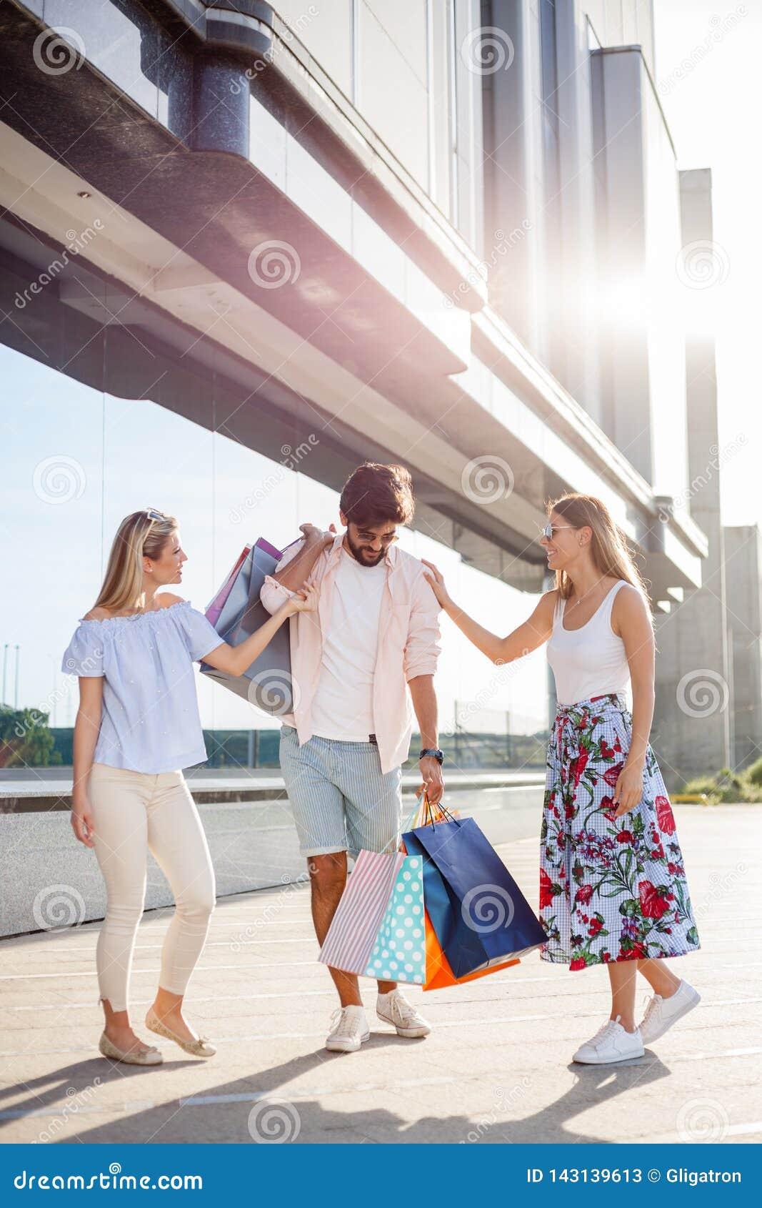 运载所有袋子的Oung人,当两个女朋友是笑和耍笑由他的边时