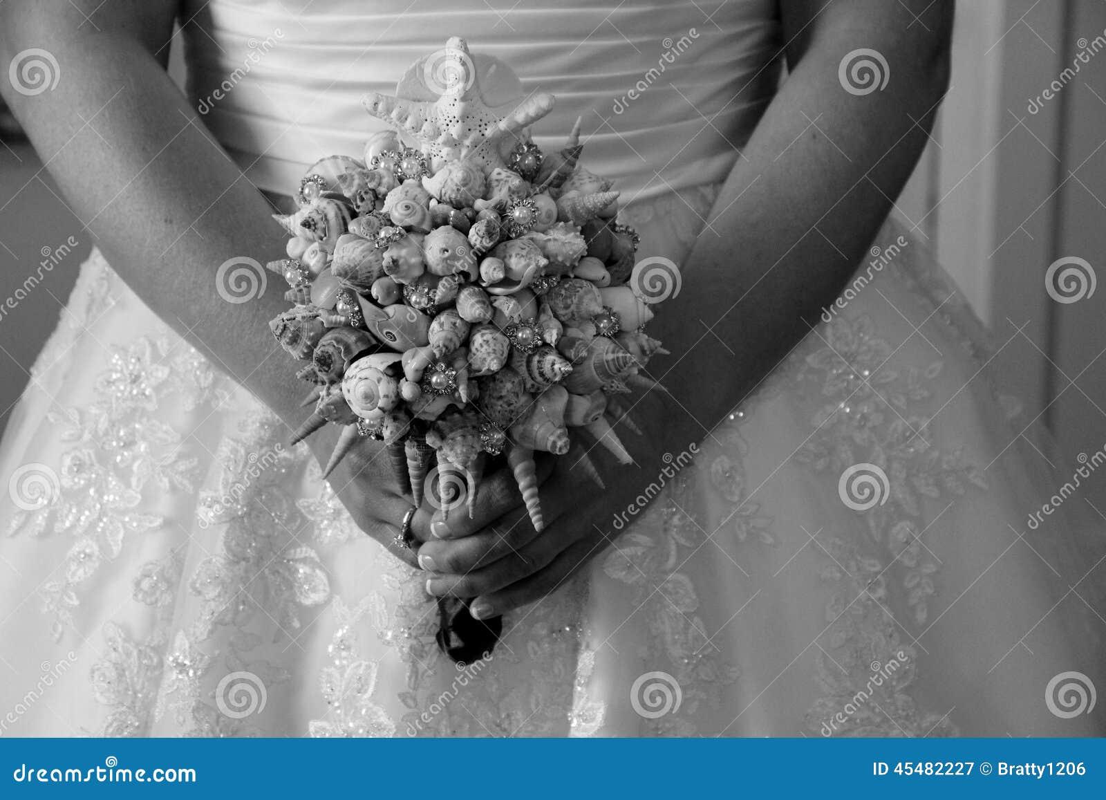 运载精心制作的贝壳花束的新娘为她的婚礼之日