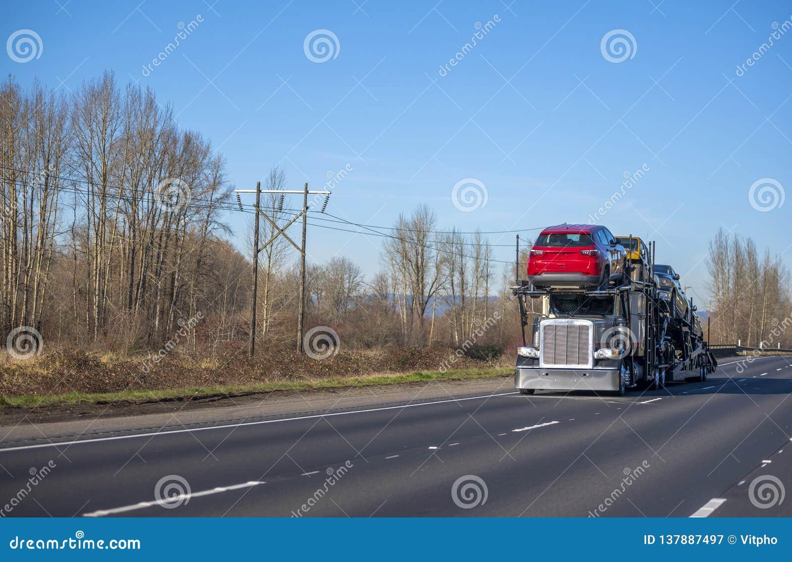 运输在半拖车的汽车和驾驶在有光秃的树的秋天路的大船具半汽车搬运工卡车