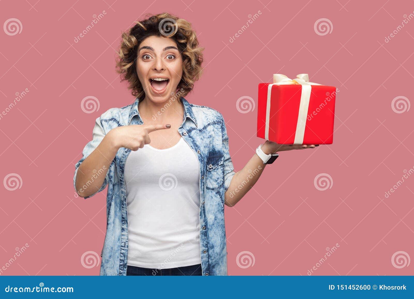 这是你的?蓝色衬衣的愉快的美丽的现代年轻女人有curlty发型身分的,拿着有打开的大礼物盒