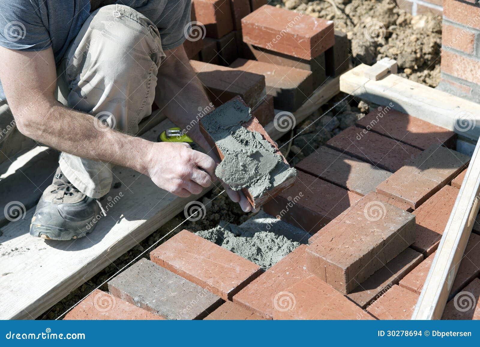 应用灰浆的砖泥工。