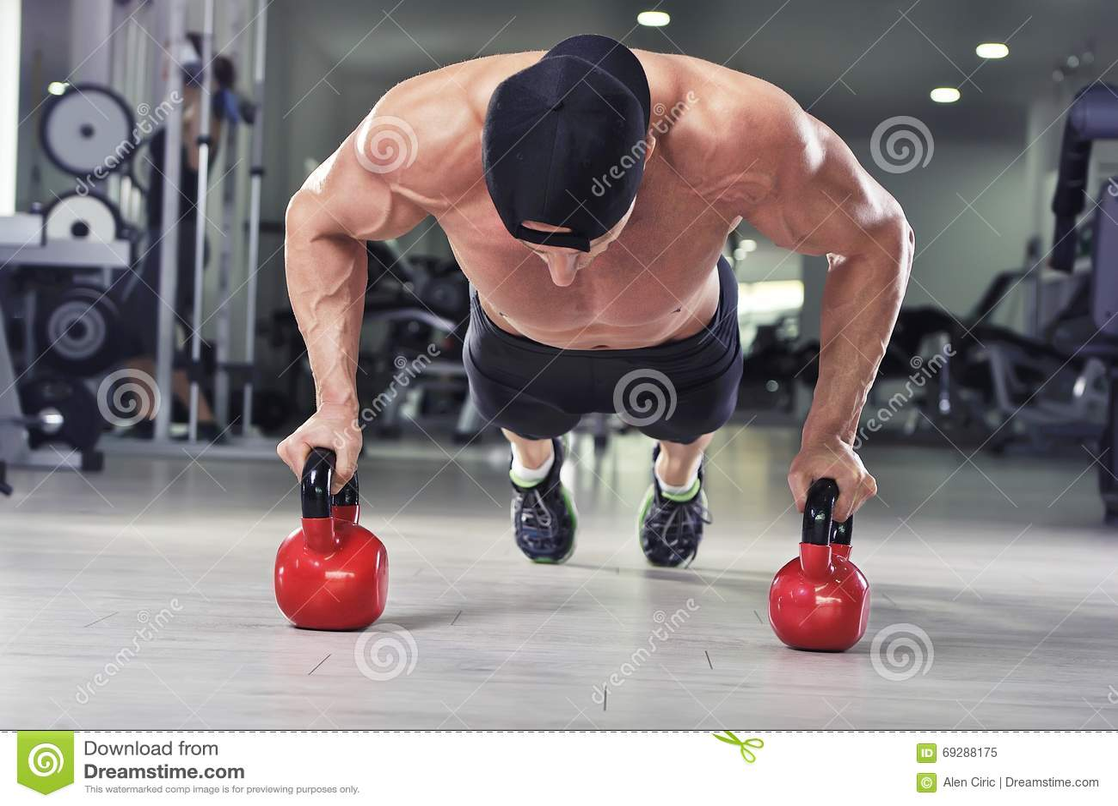 进行俯卧撑的英俊的强有力的运动人与水壶响铃