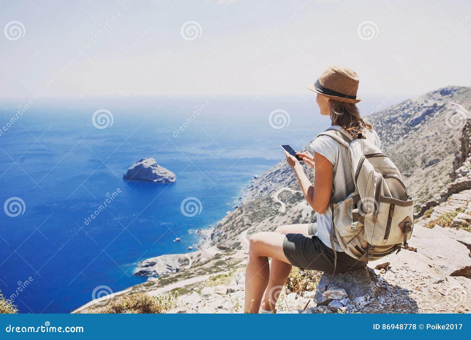 远足使用巧妙的电话的妇女采取照片、旅行和活跃生活方式概念