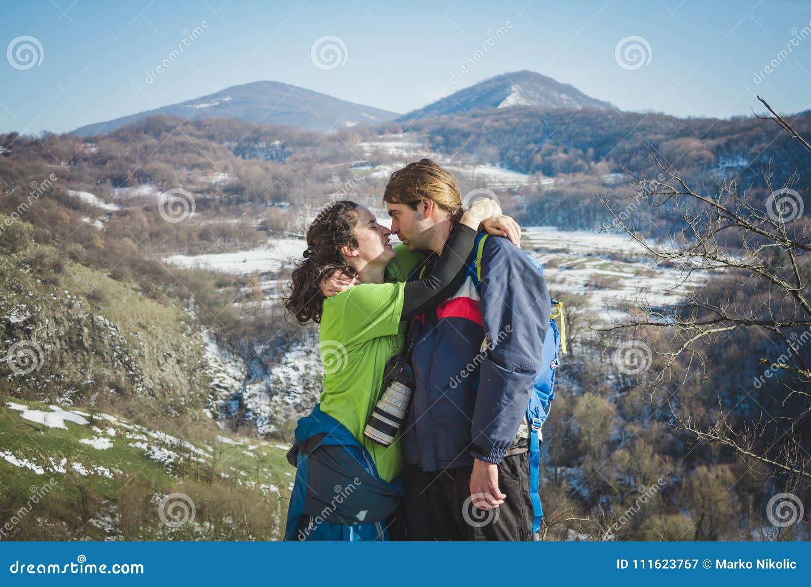 远足者和照相机夫妇有背包的在山峭壁的