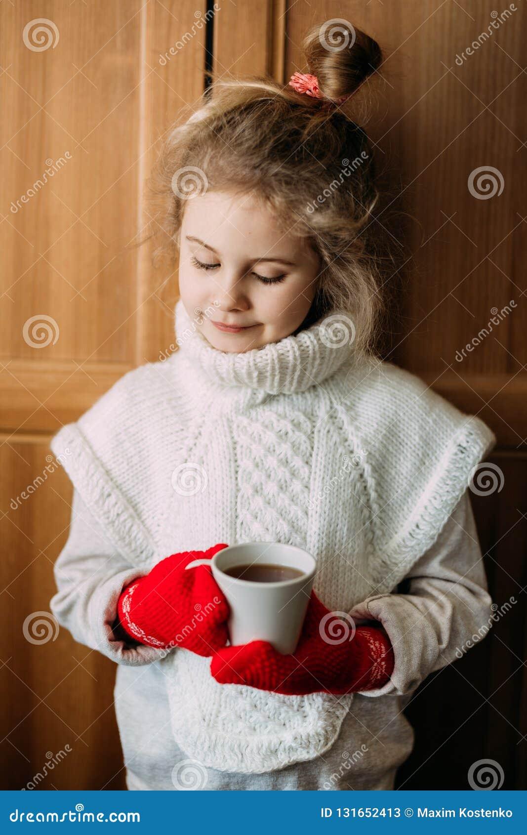 迷人的七岁的女孩喝温暖的茶,站立在窗口旁边 她穿一件温暖的被编织的毛线衣,她
