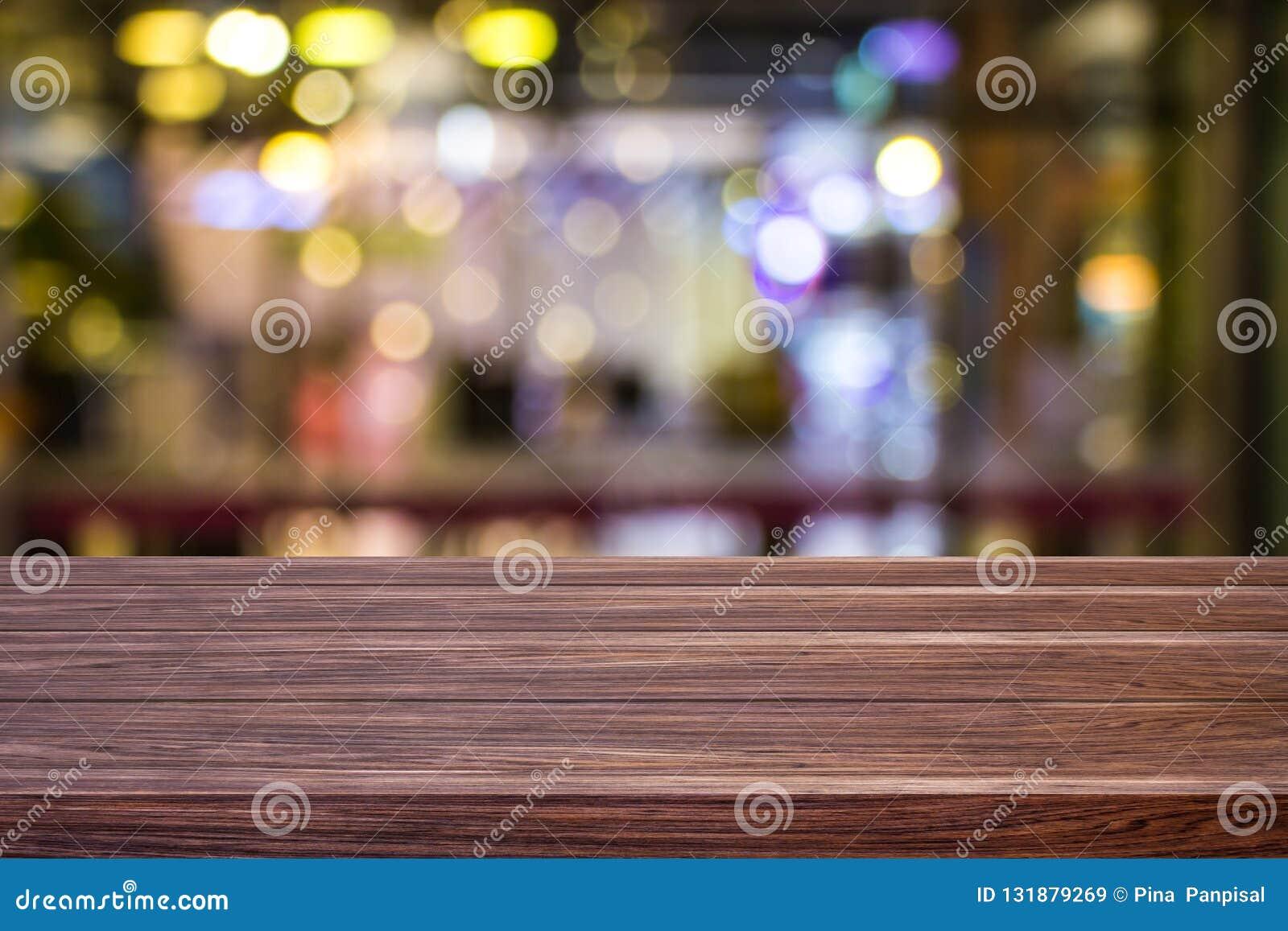 迷离咖啡馆餐馆或咖啡馆空黑暗的木桌有蒙太奇产品的被弄脏的轻的金bokeh抽象背景