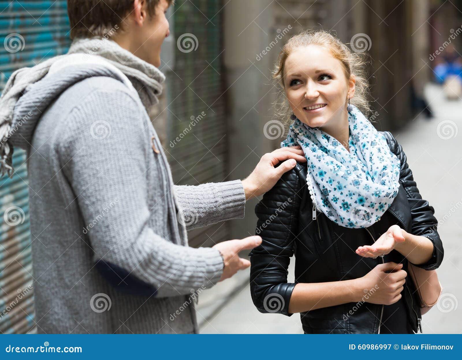 追逐喜悦的女孩的好男学生在室外日期
