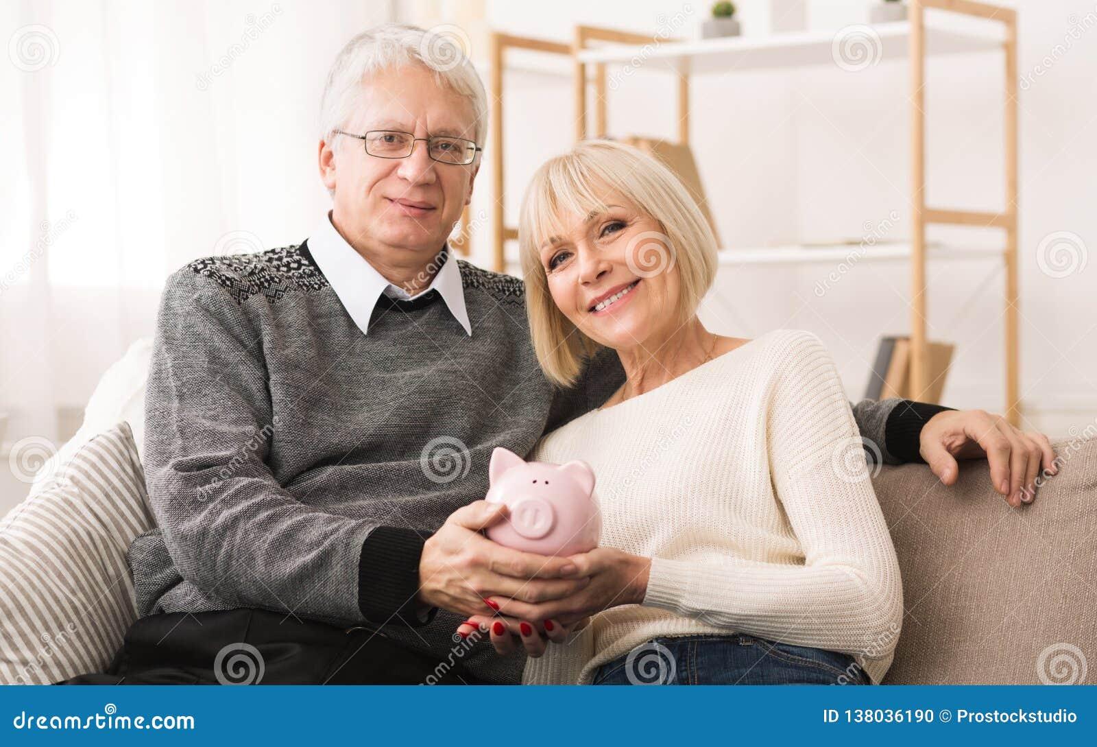 退休储款 在家拿着piggybank的资深夫妇