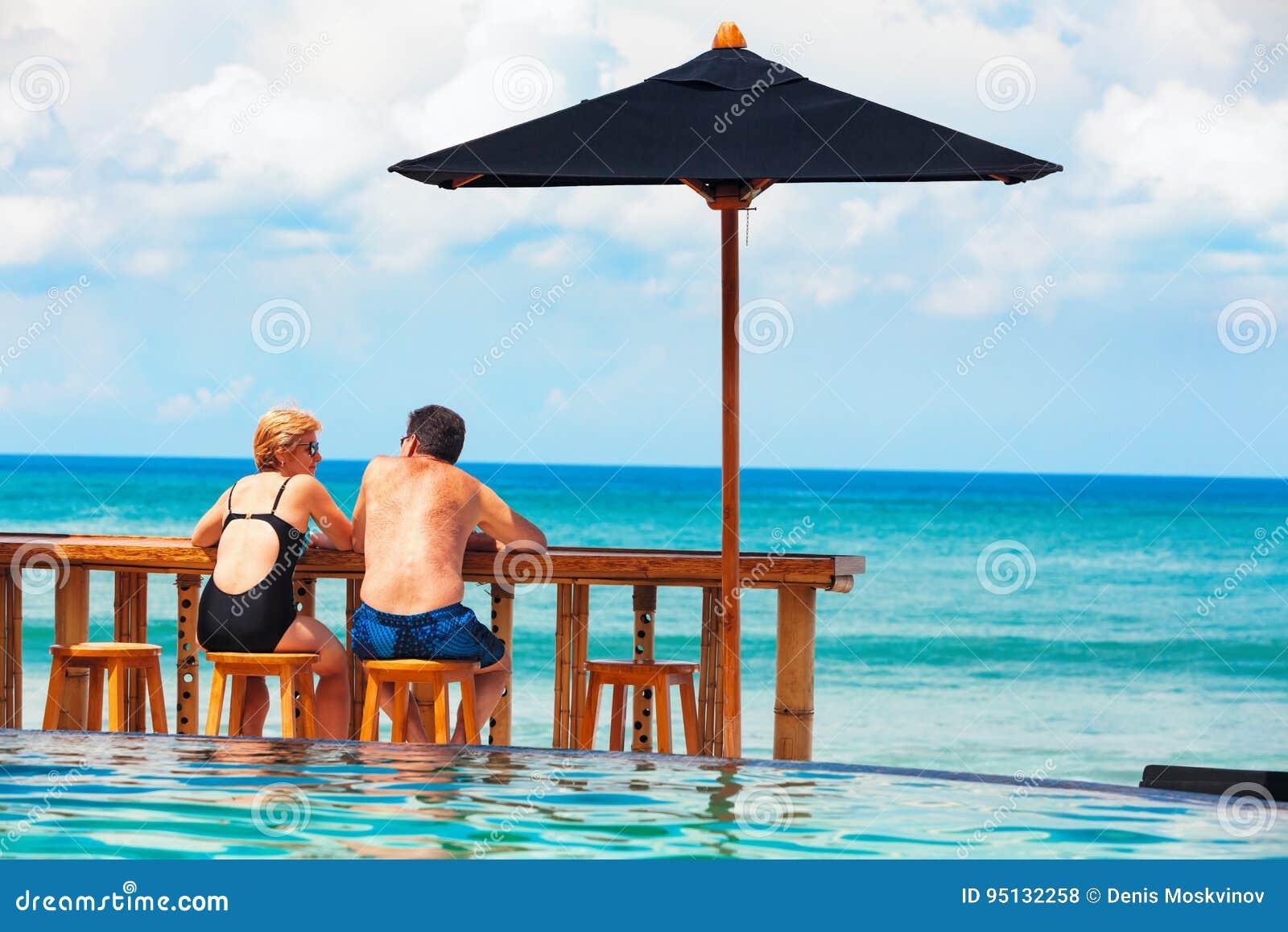 退休的成熟夫妇松弛海滩游泳池