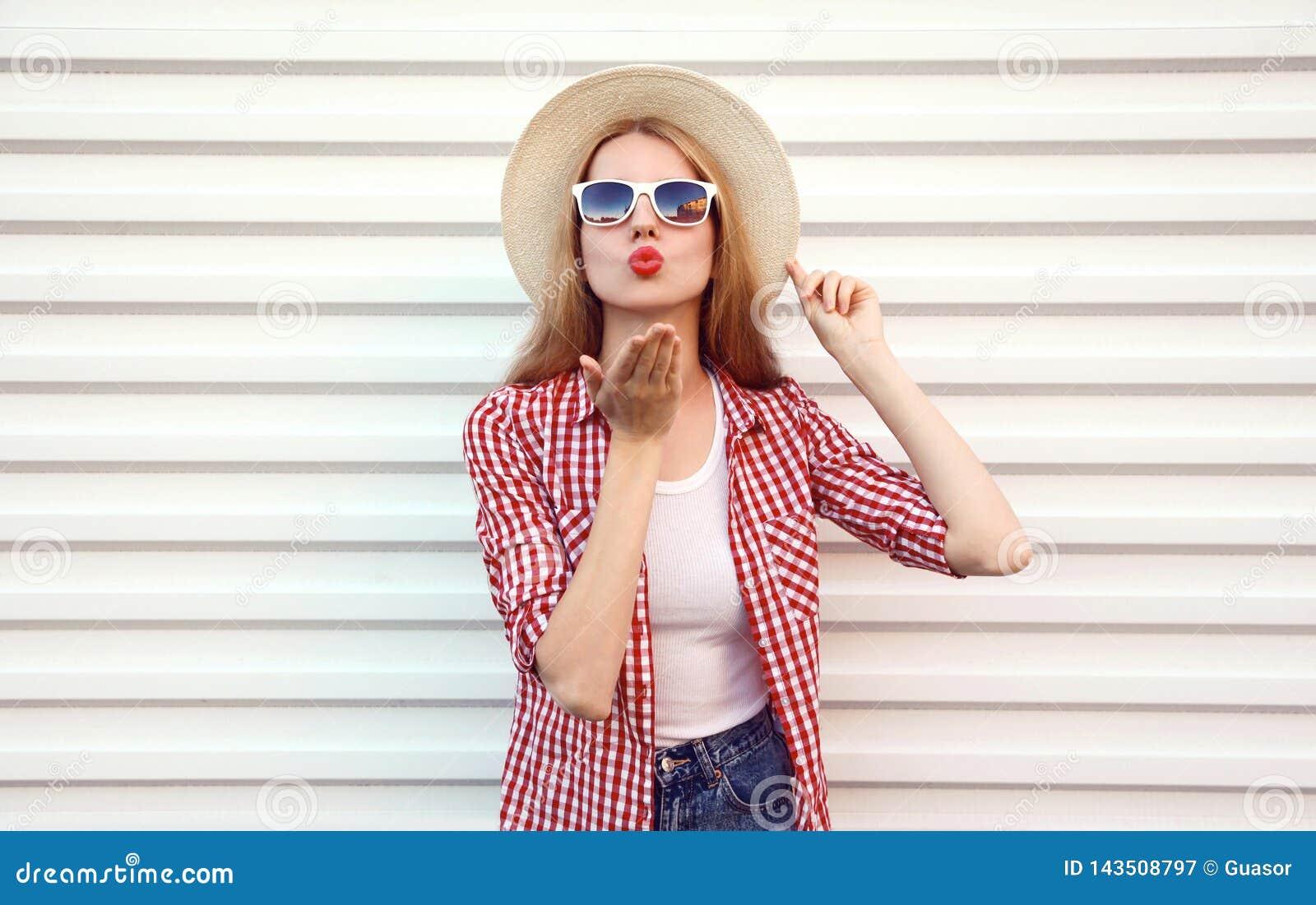 送甜空气亲吻的画象年轻女人吹在夏天回合草帽,在白色墙壁上的方格的衬衣的红色嘴唇