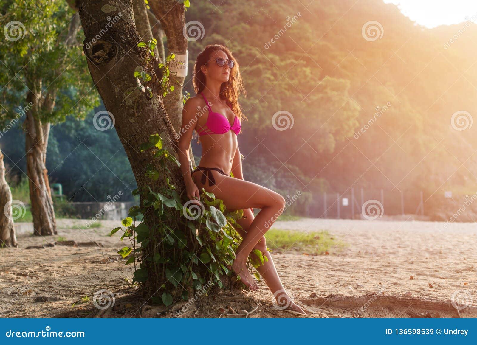 适合少妇全长画象桃红色胸罩和黑内裤的坐树干佩带的太阳镜与