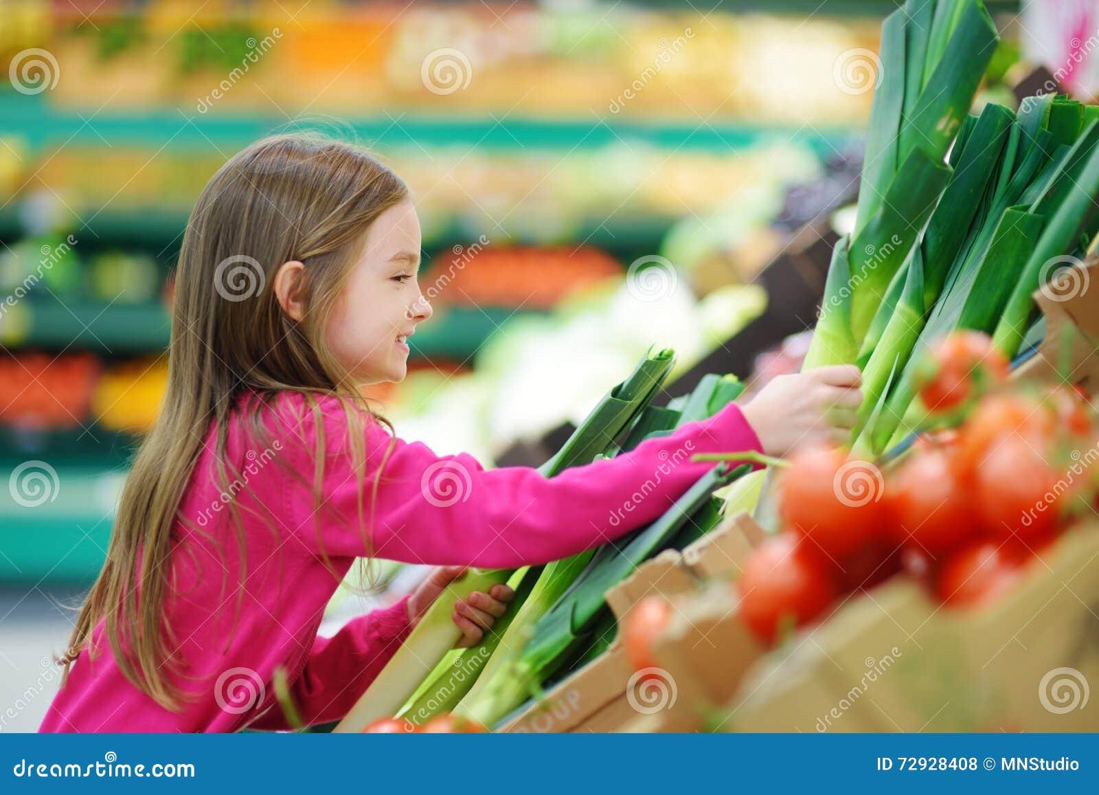 选择一个韭葱的小女孩在食品店或超级市场