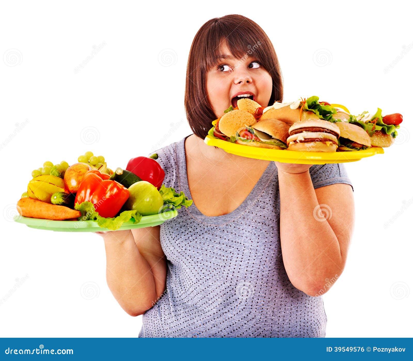 选择在果子和汉堡包之间的妇女。