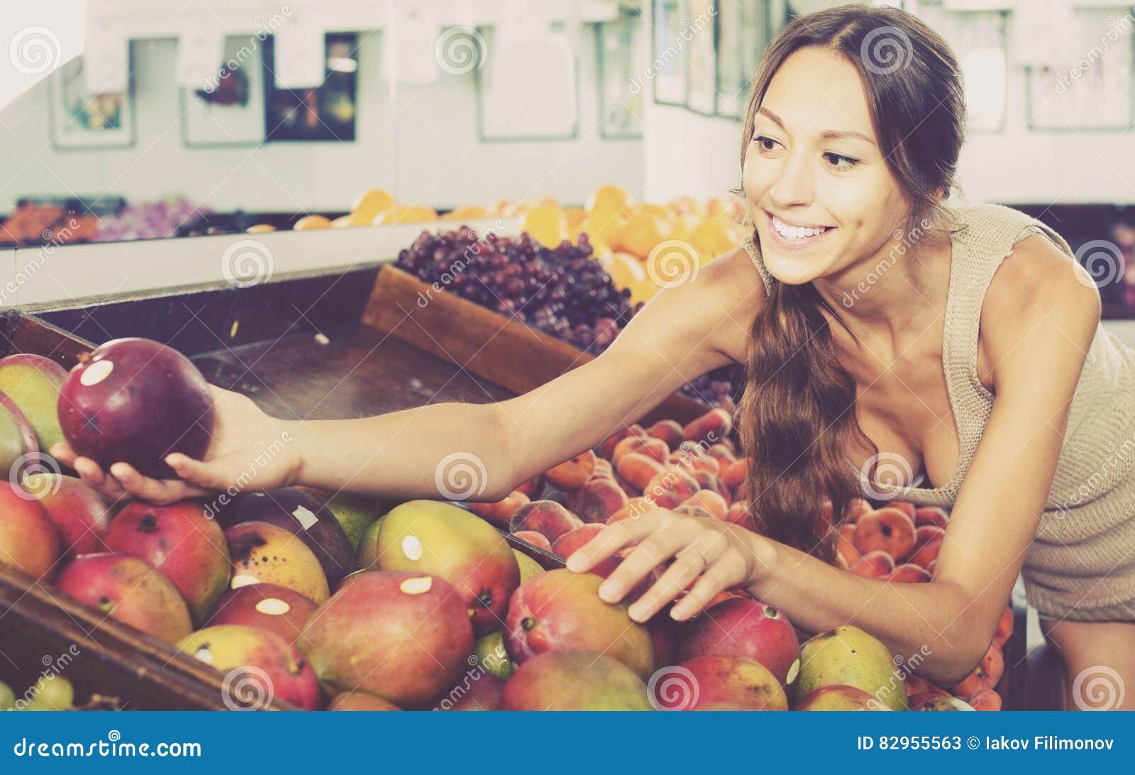 选择成熟芒果的愉快的少妇顾客