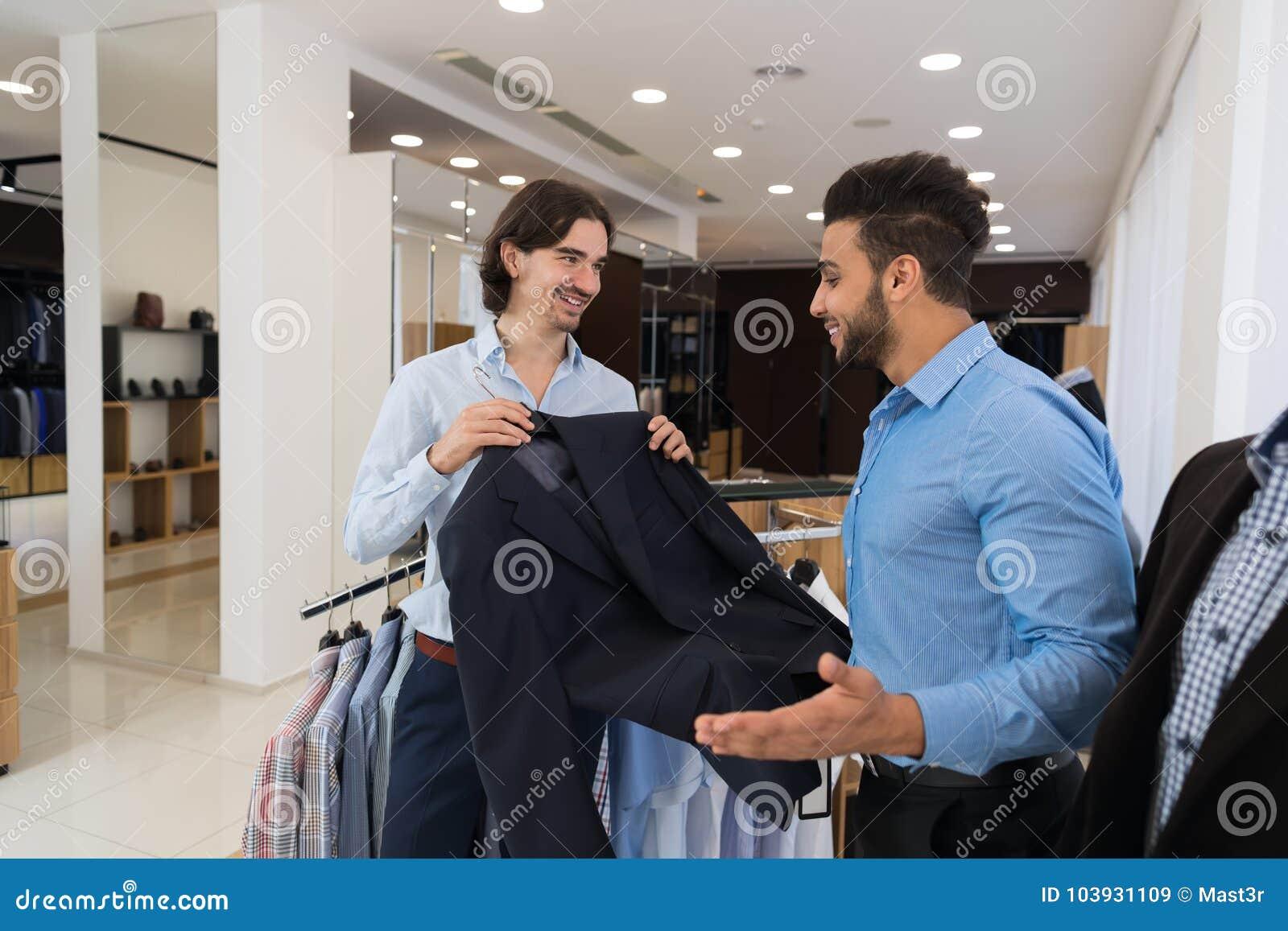 选择新的衣服的年轻商人在零售店的购物期间