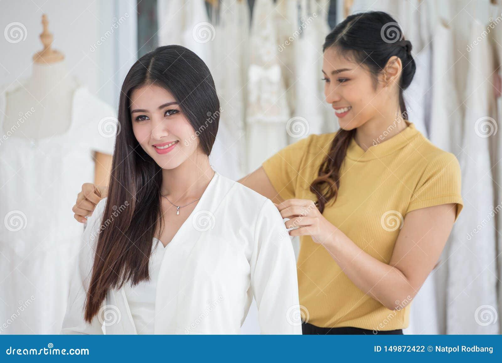 选择有设计师的年轻亚裔新娘秀丽画象婚纱做在时尚商店婚姻的沙龙的礼服,豪华