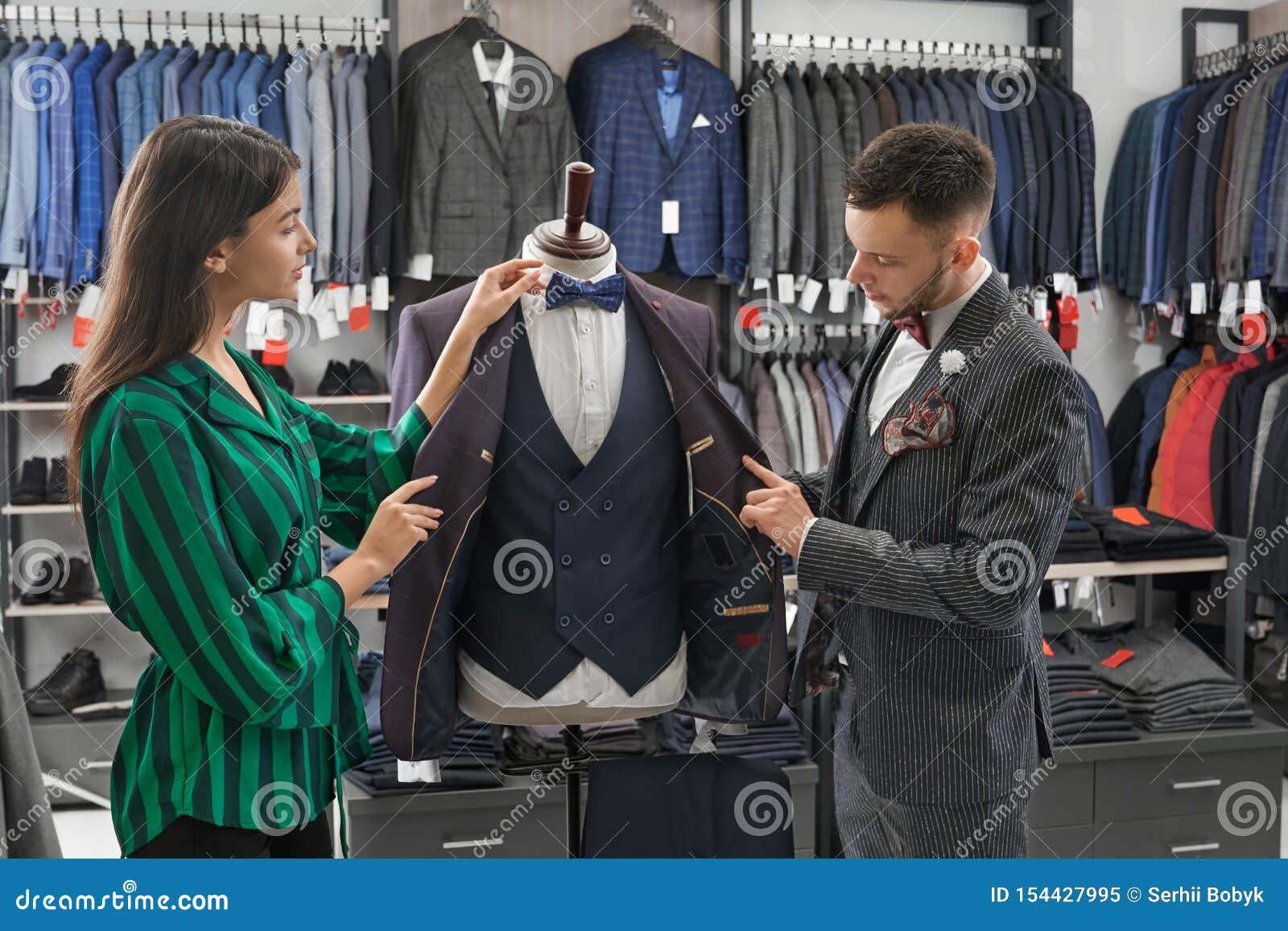 选择衣服的商店顾问和人,看在时装模特