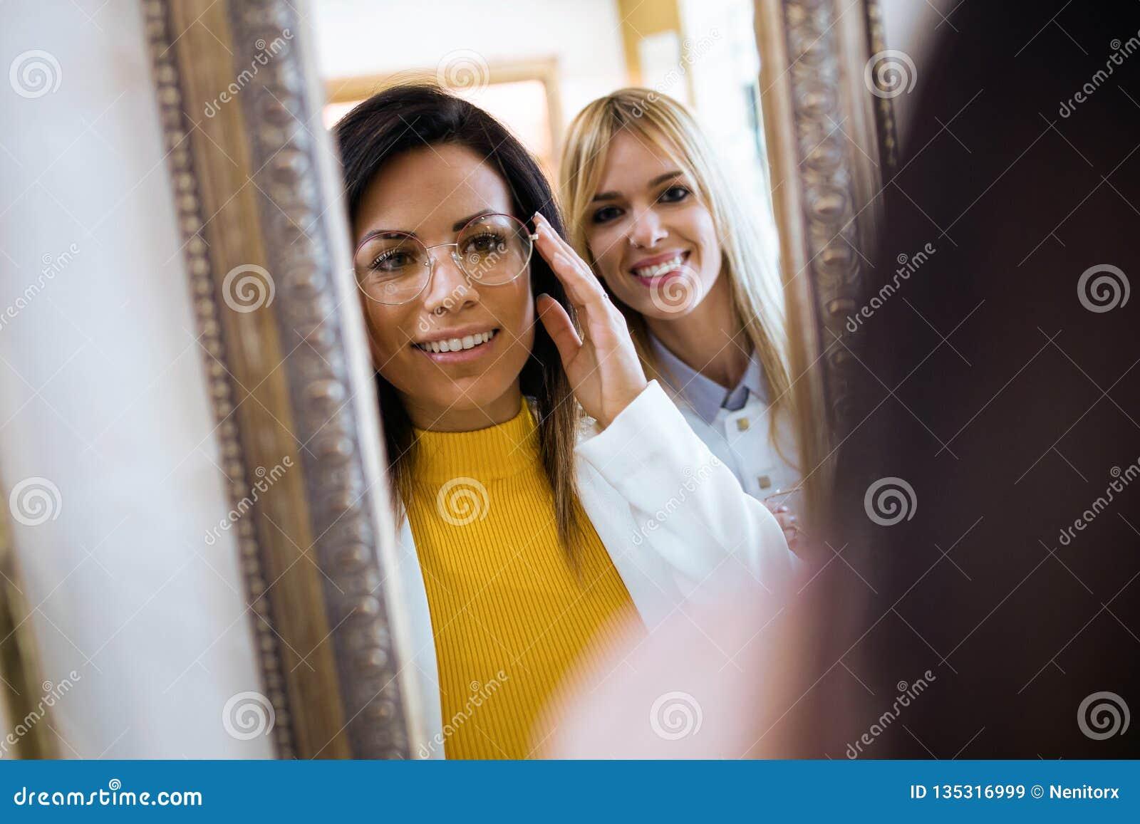 选择镜片和看镜子的愉快的年轻女人,当站立近在视觉商店时的可爱的年轻眼医