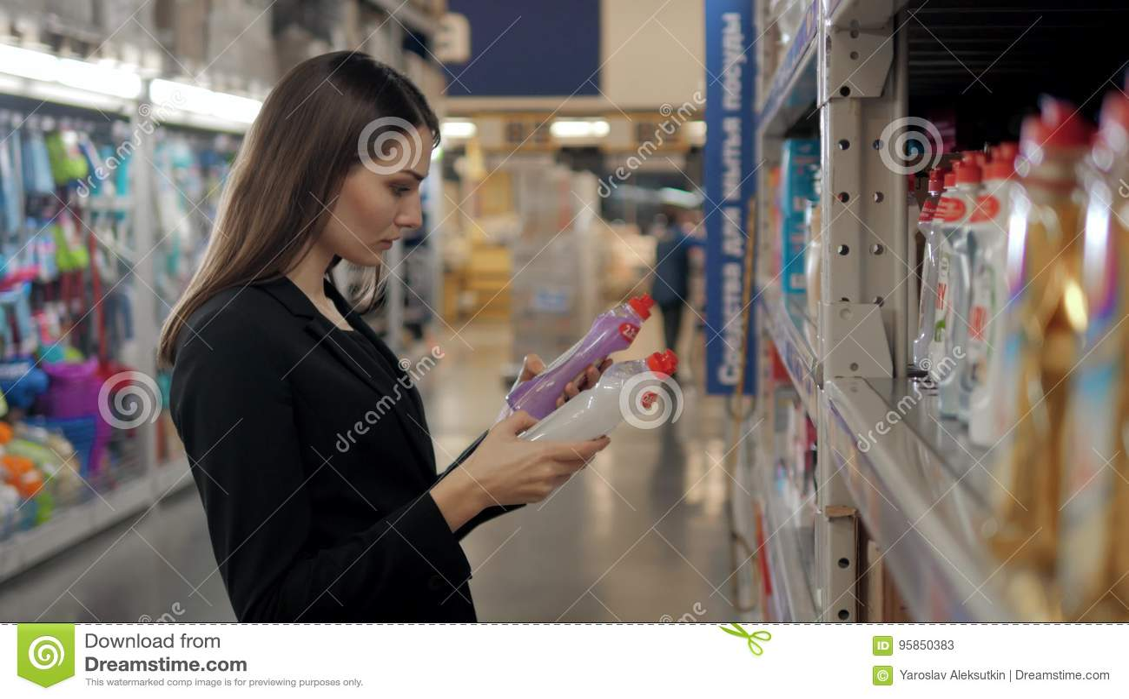 选择洗涤剂的妇女在杂货店 女实业家在超级市场