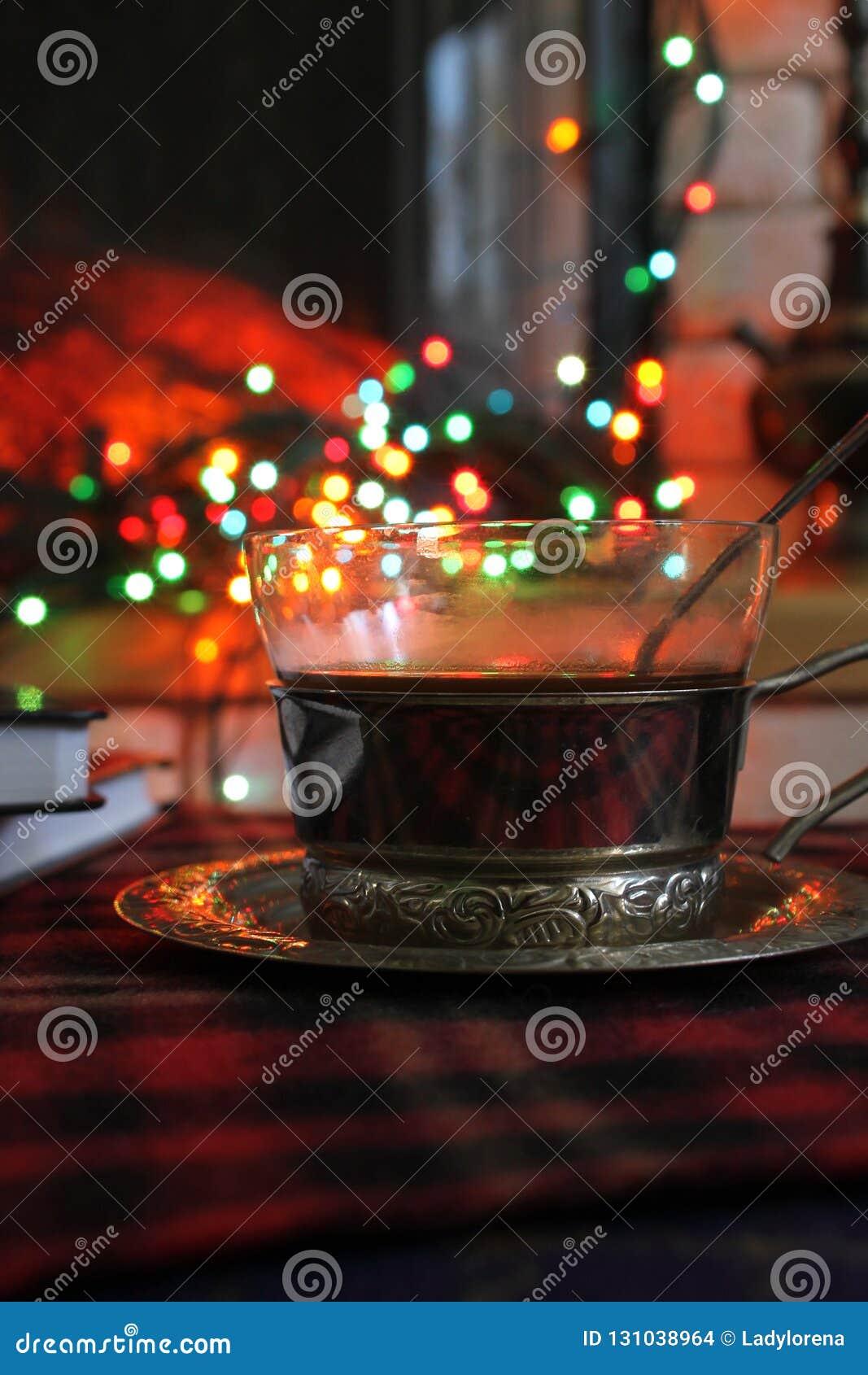 透明茶在钢杯座的在一本灼烧的壁炉和圣诞节诗歌选的背景