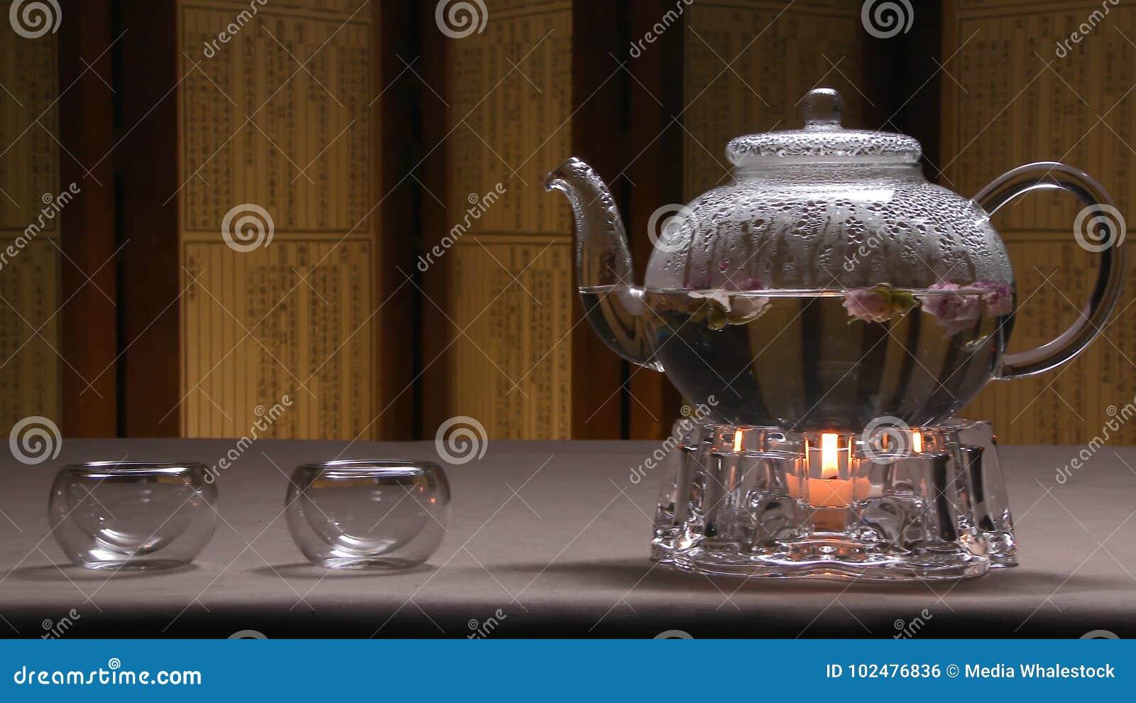 透明茶壶水壶的美好的温暖的图片用在一张桌上的鲜美绿色红茶与蜡烛 玻璃水壶