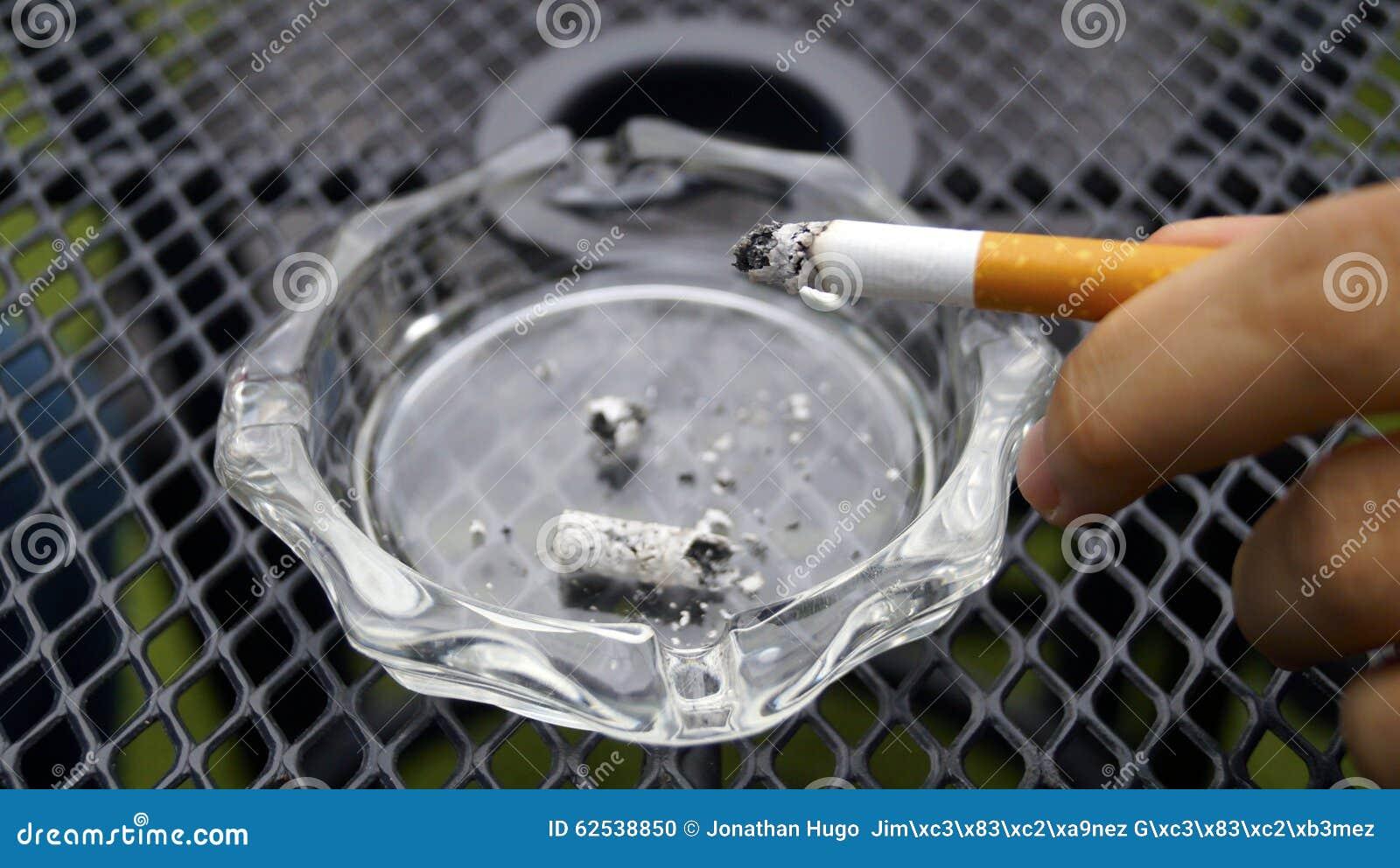 递在cigarrete的hilding的光在灰盘