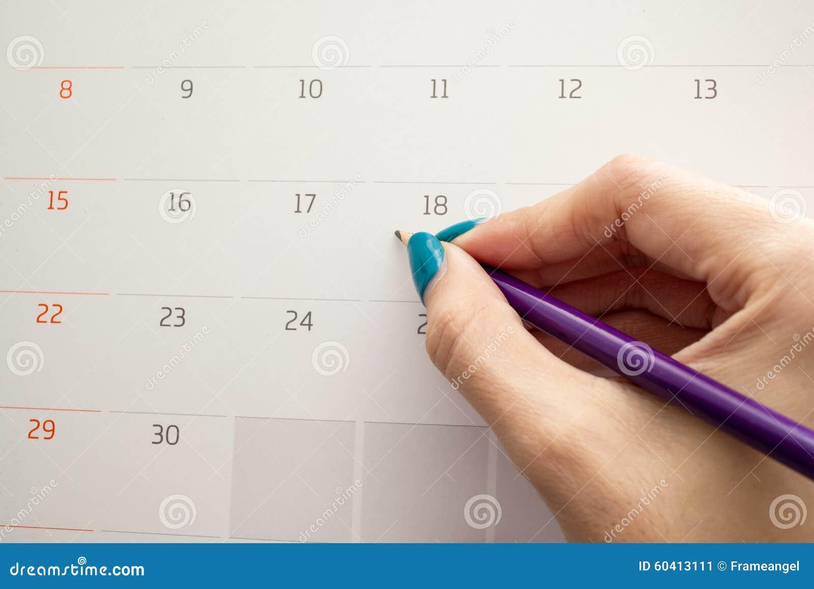 递拿着在日历的铅笔做的任命importa