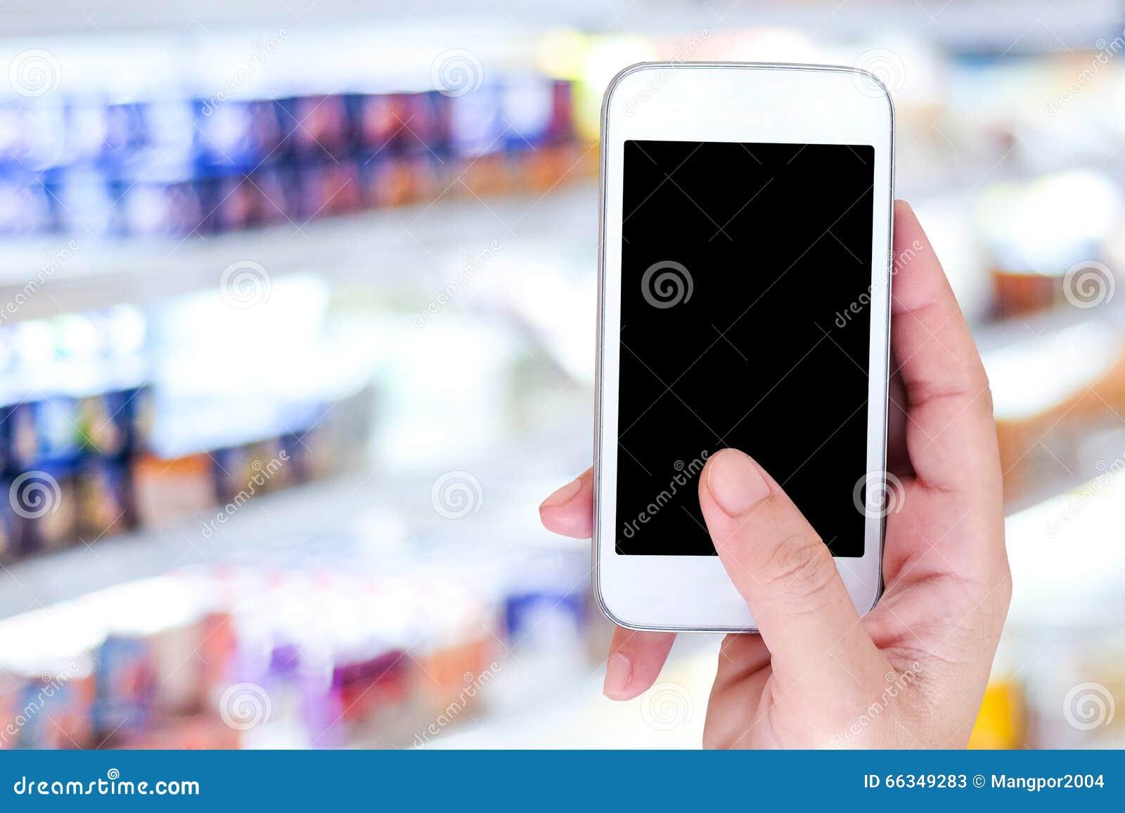 递拿着在迷离超级市场背景的巧妙的电话