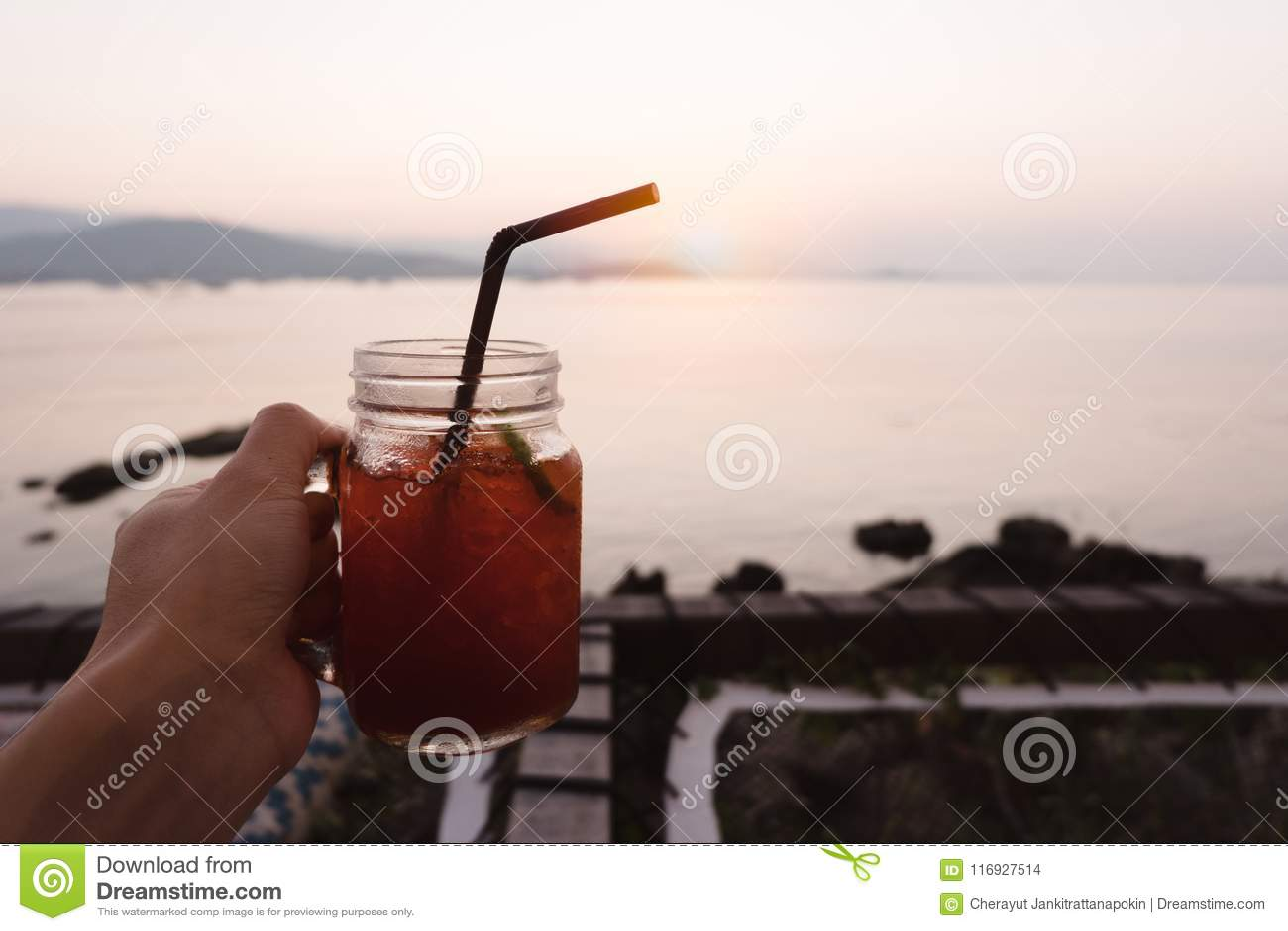 递拿着杯柠檬在热带海海滩的冰茶在太阳