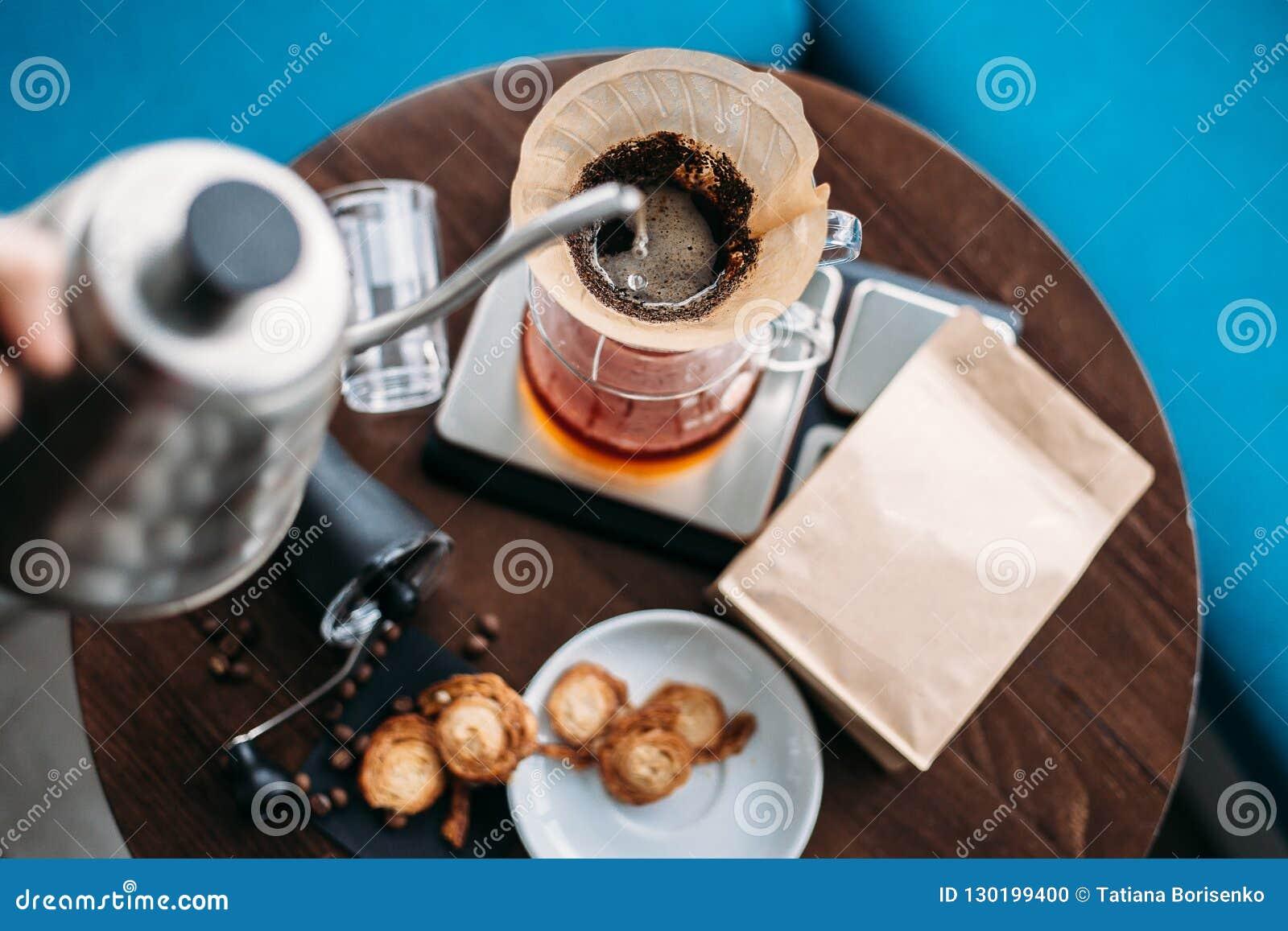 递滴水咖啡,在咖啡渣的Barista倾吐的水与fi