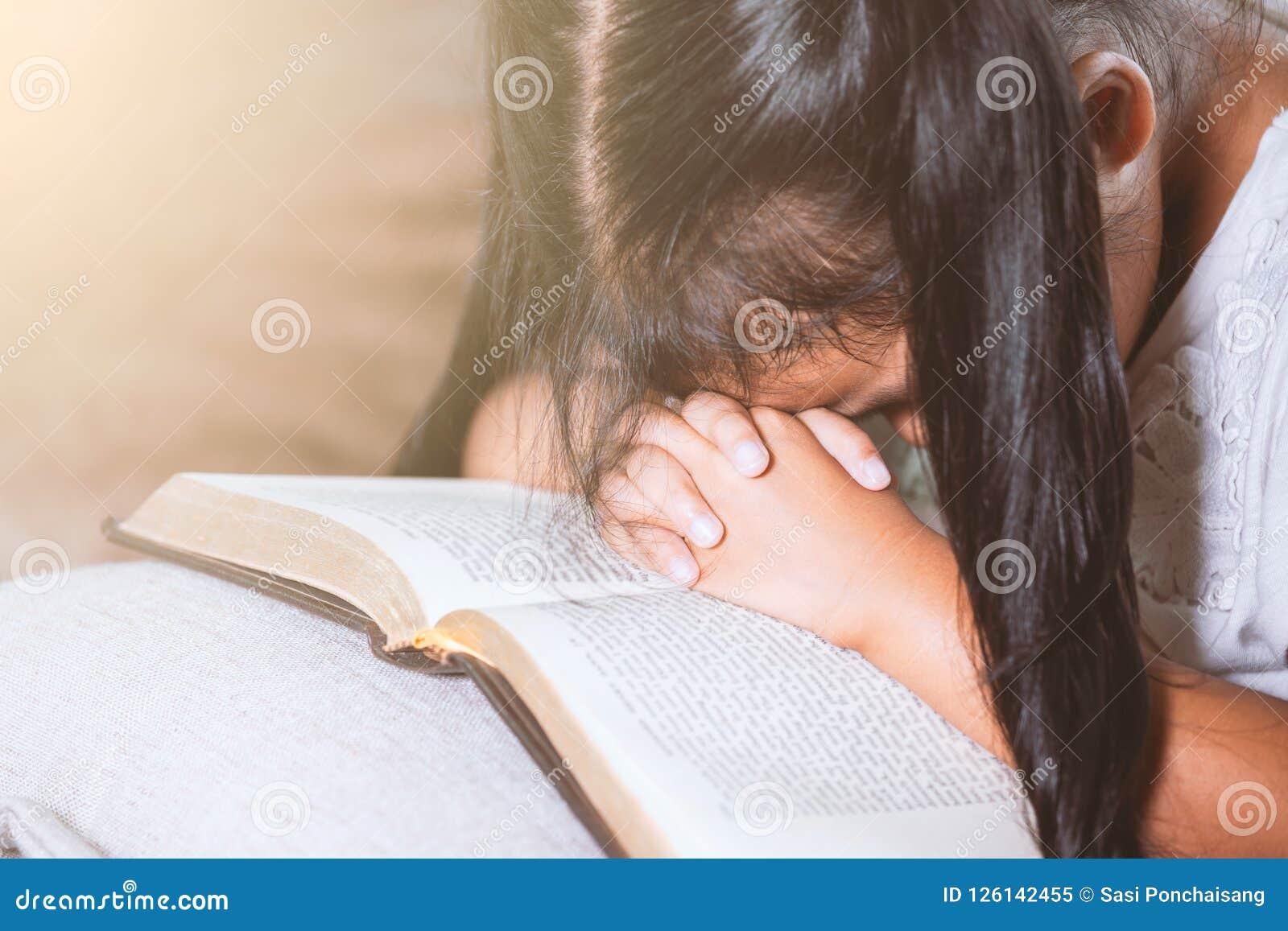 逗人喜爱的亚裔小孩女孩闭上了她的眼睛并且折叠了她的手