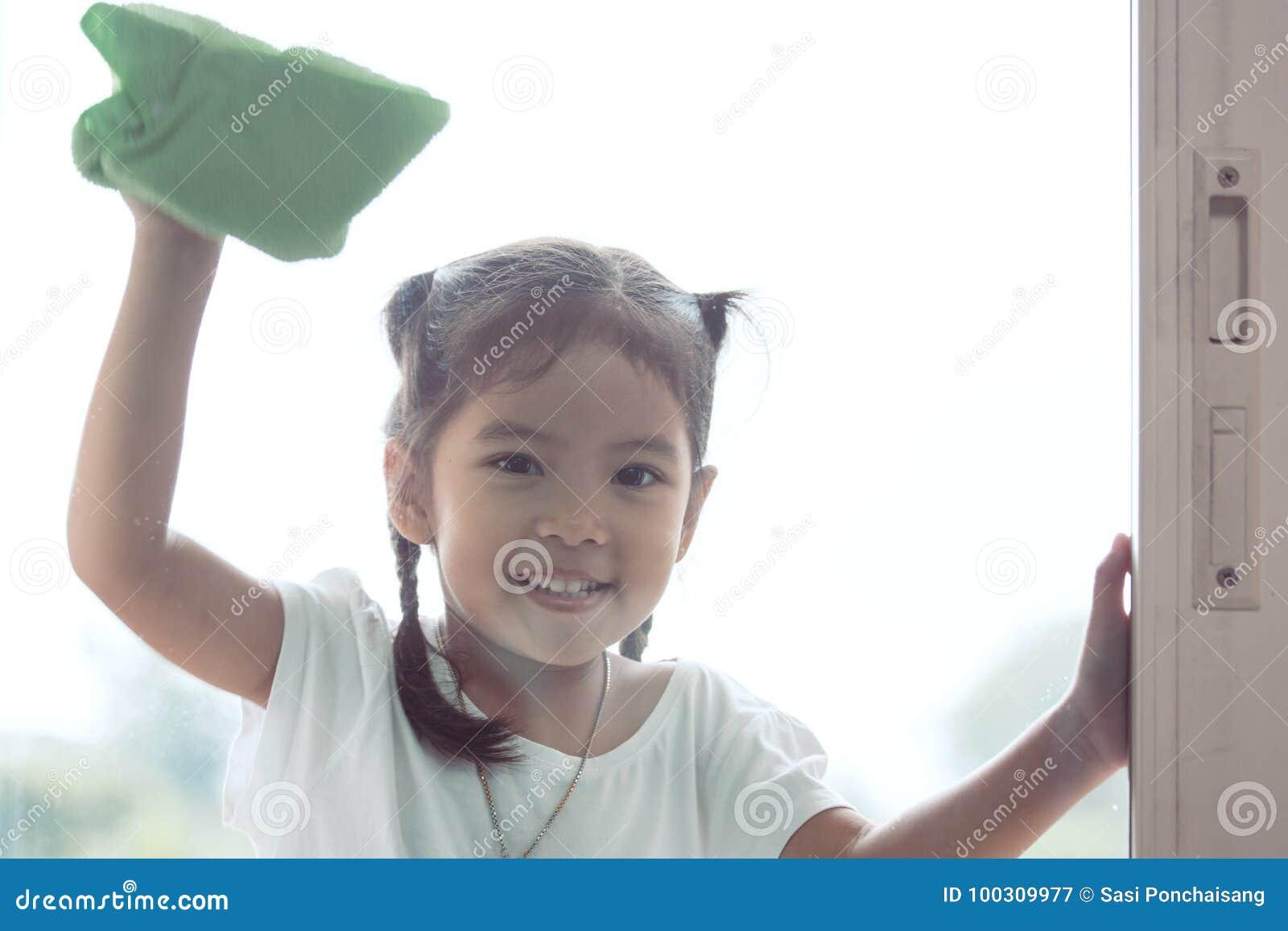逗人喜爱的亚裔清洗窗口的小孩女孩帮助的父母