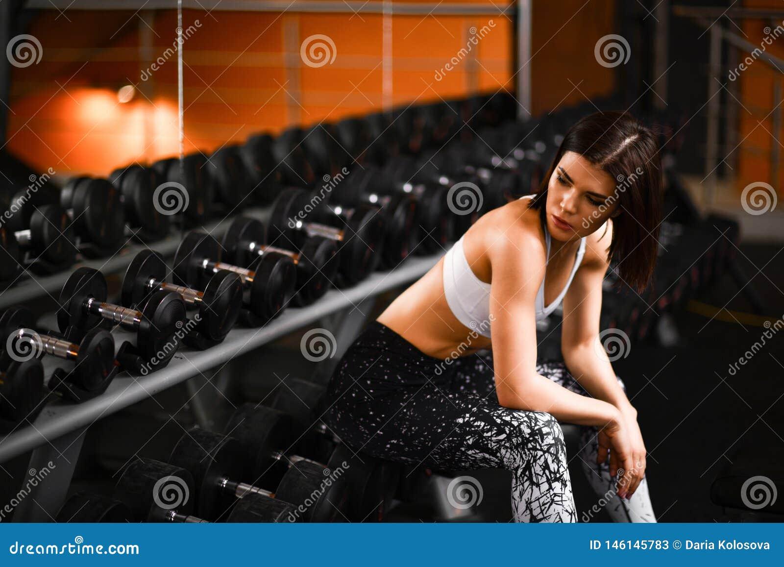 逗人喜爱的体育女孩浅黑肤色的男人在健身房坐在镜子附近在bowties旁边 在训练的断裂