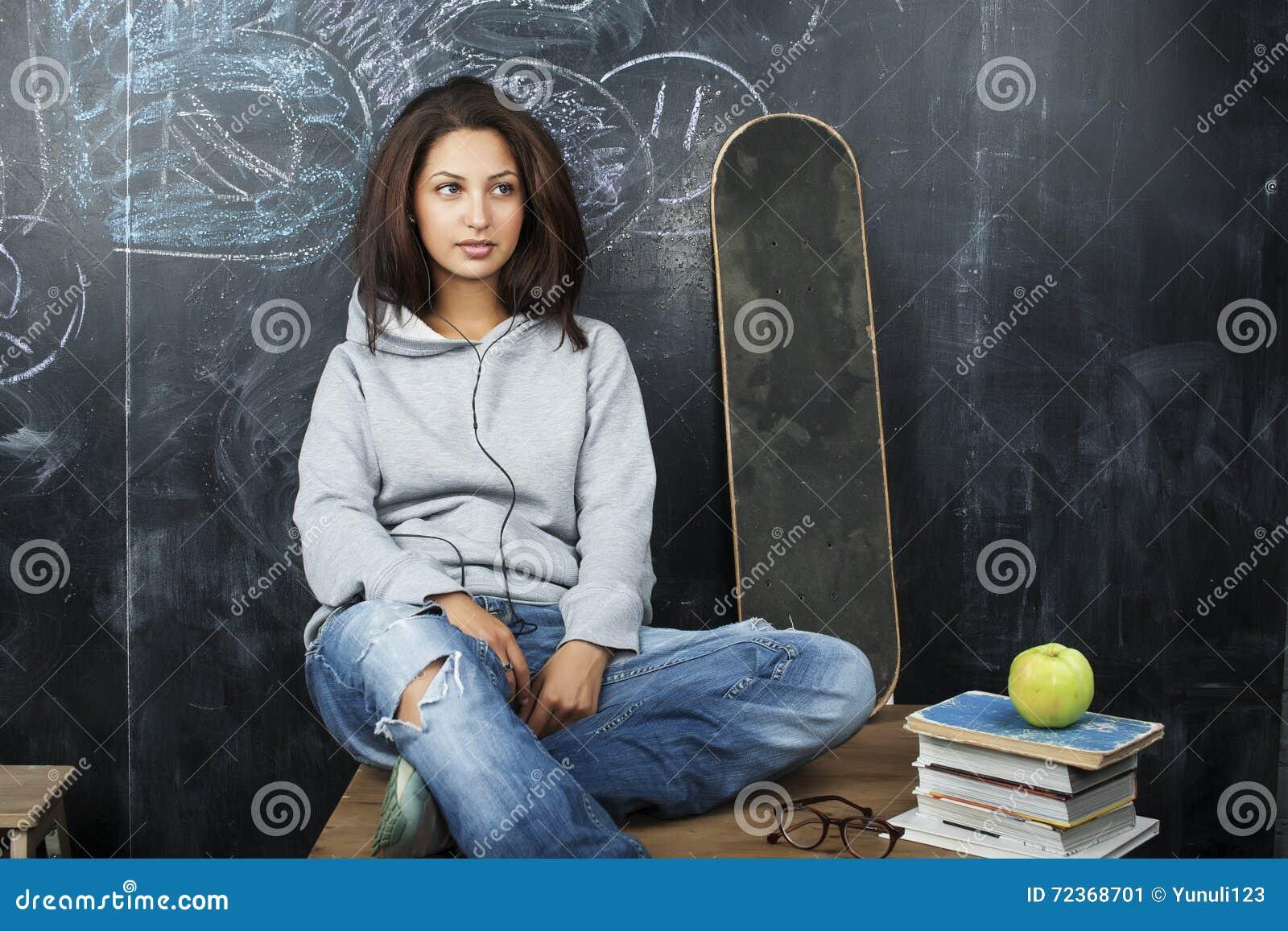 年轻逗人喜爱的十几岁的女孩在黑板就座的教室在桌微笑