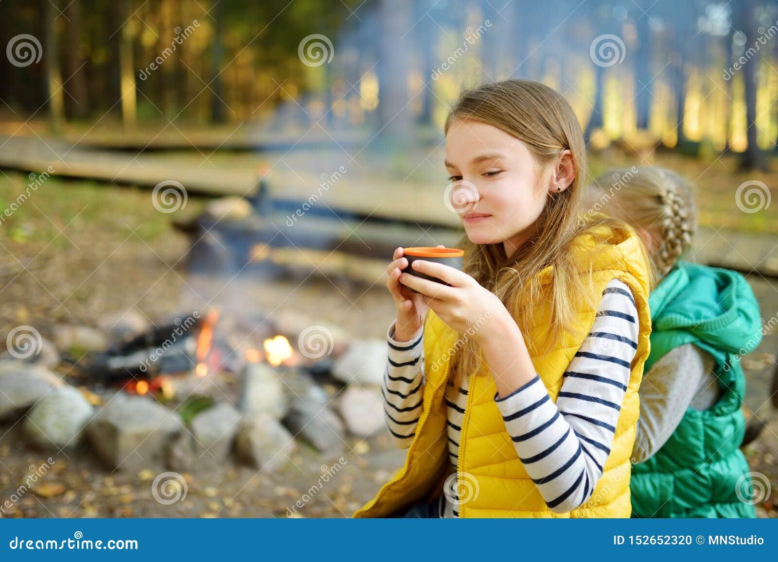 逗人喜爱的在棍子的少女饮用的茶和烤蛋白软糖在篝火 孩子获得乐趣在阵营火 野营与孩子