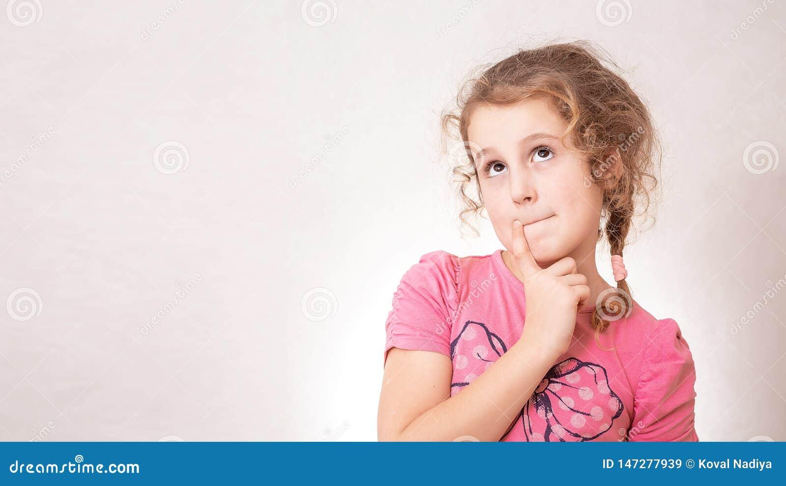逗人喜爱的女孩与卷发的八岁在灰色背景
