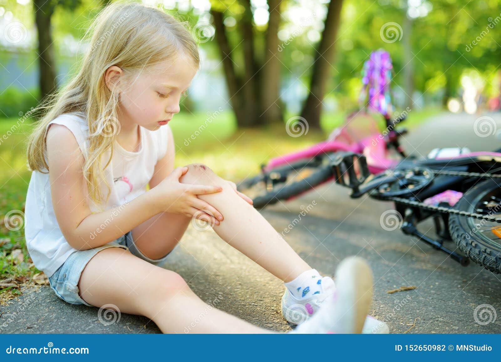逗人喜爱的女孩坐地面在落她的自行车在夏天公园以后 受到伤害的孩子,当骑自行车时